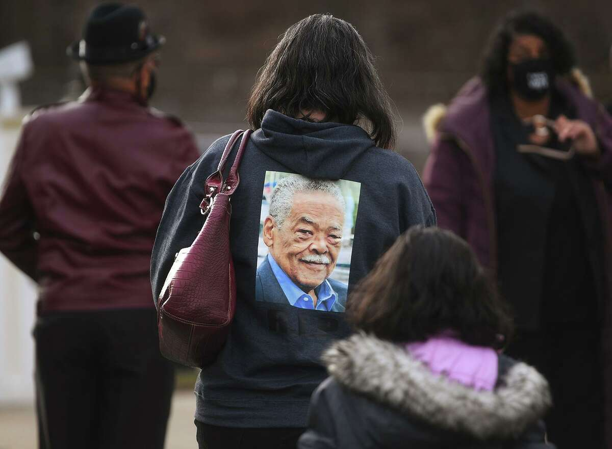 Jennifer Bush, neice of deceased State Senator Ed Gomes, wears a sweatshirt printed with his photo as she attends his funeral service at Blessed Sacrament RC Church on Union Avenue in Bridgeport, Conn. on Wednesday, December 30, 2020.