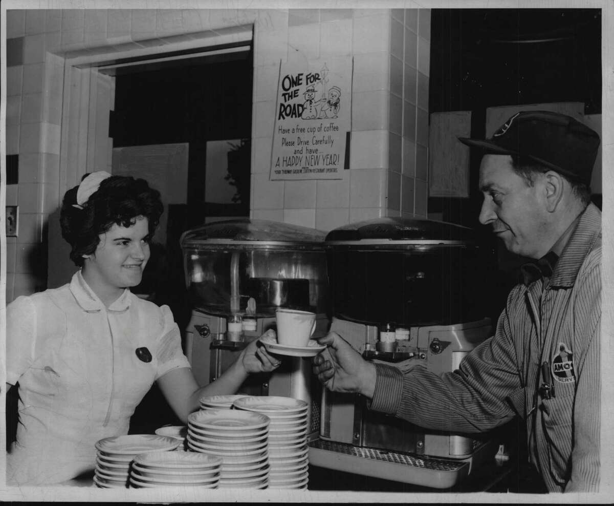 On Dec. 30, 1951, waitress Claudia Bingham of Brainard, an employee at the Thruway's Savarin restaurant at the Rensselaer Service Area, smilingly hands a cup of coffee to James Rector of Niverville, manager of the American Oil Service Co. service station there. Free coffee is meant to encourage safe and sane driving. (Times Union Archive)