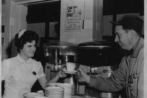 New York - Waitress Claudia Bingham of Brainard, an employee at the Thruway's Savarin restaurant at the Rensselaer Service Area, smilingly hands a cup of coffee to James Rector of Niverville, manager of the American Oil Service Co. service station there. Motorists traveling the Thruway from 10pm tomorrow to 7am Monday again will be provided with free coffee to encourage safe and sane driving. December 30, 1951 (Times Union Archive)