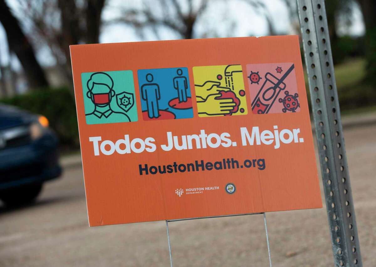 A Spanish COVID-19 prevention sign by Houston Health Department is photographed at a free self-nasal swab drive-thru Covid-19 testing site Tuesday, Dec. 29, 2020, at Park Place Regional Library in Houston. City officials are encouraging the public to get tested if they have been gathring or flying recently.