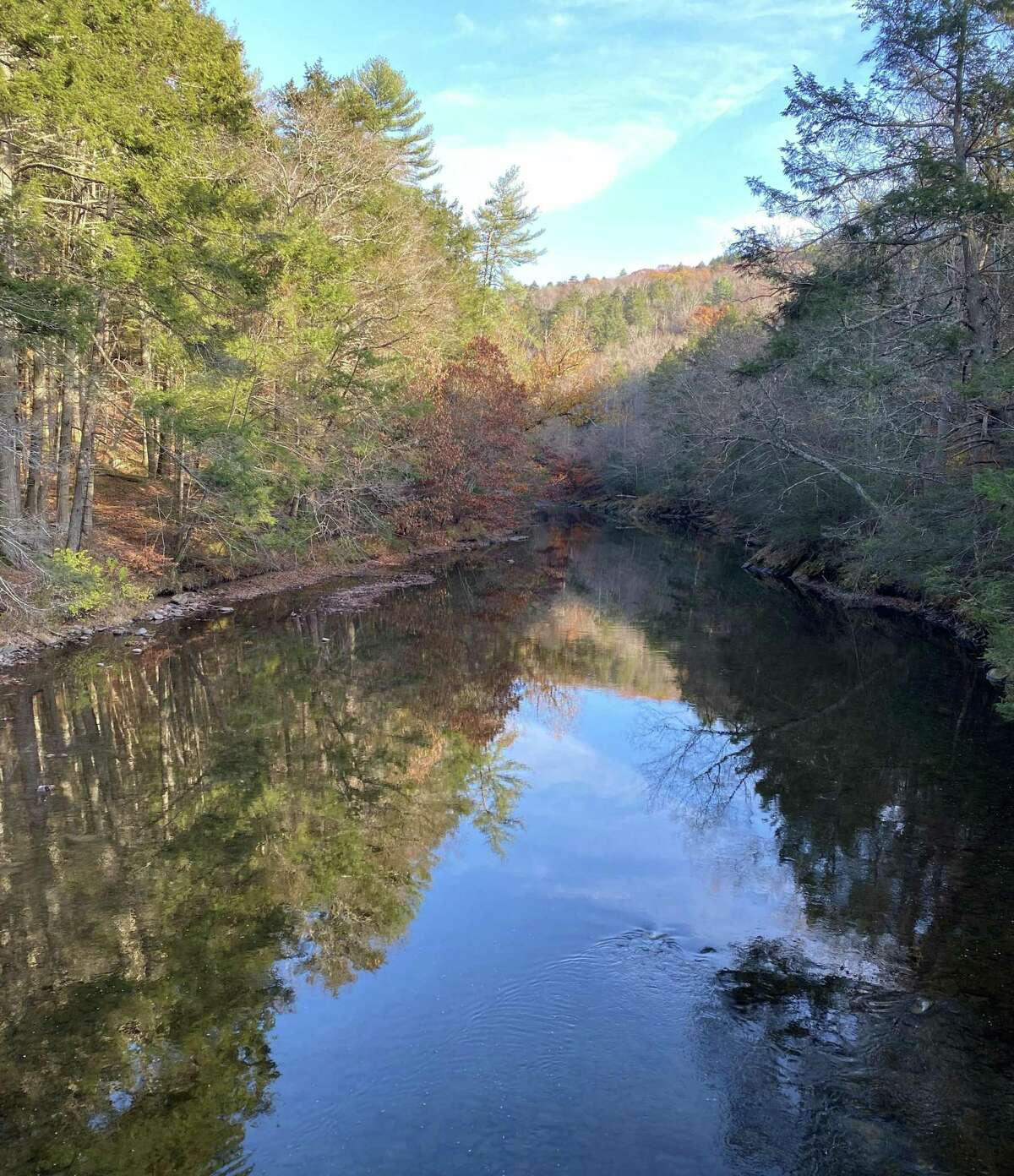 The Shepaug River, as seen from Hauser Footbridge at Steep Rock Preserve, in Washington reflects late autumnal splendor.