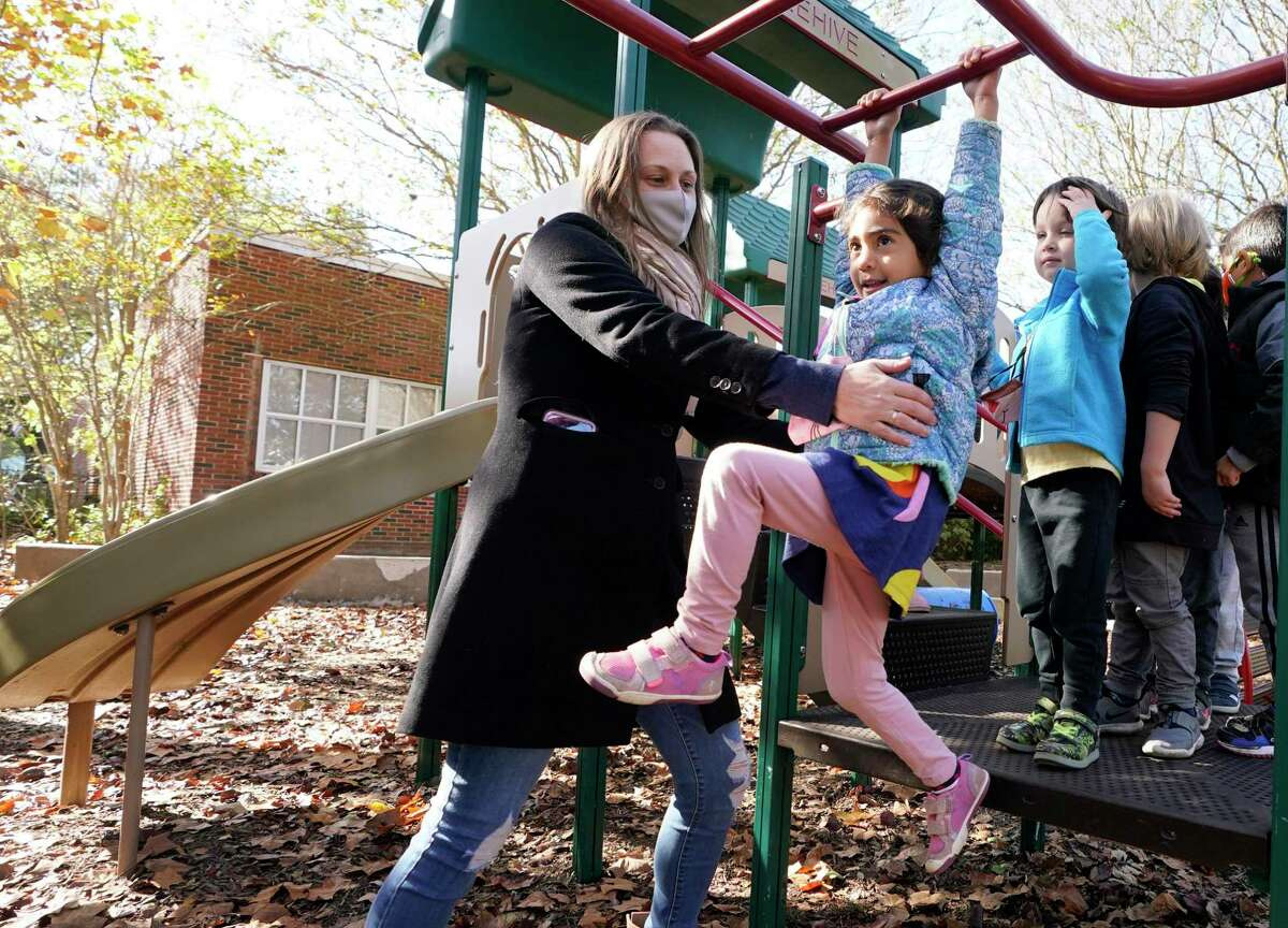 Jennifer Jacobs, school coordinator, helps Lilia Farshadi, 4, as the children play outside at the Beehive Parent Child Center, 3756 University Blvd., Thursday, Dec. 17, 2020 in Houston. The cooperative is on the campus of West University Elementary School. Houston ISD is ending its partnership with several private early education organizations operating out of district campuses.