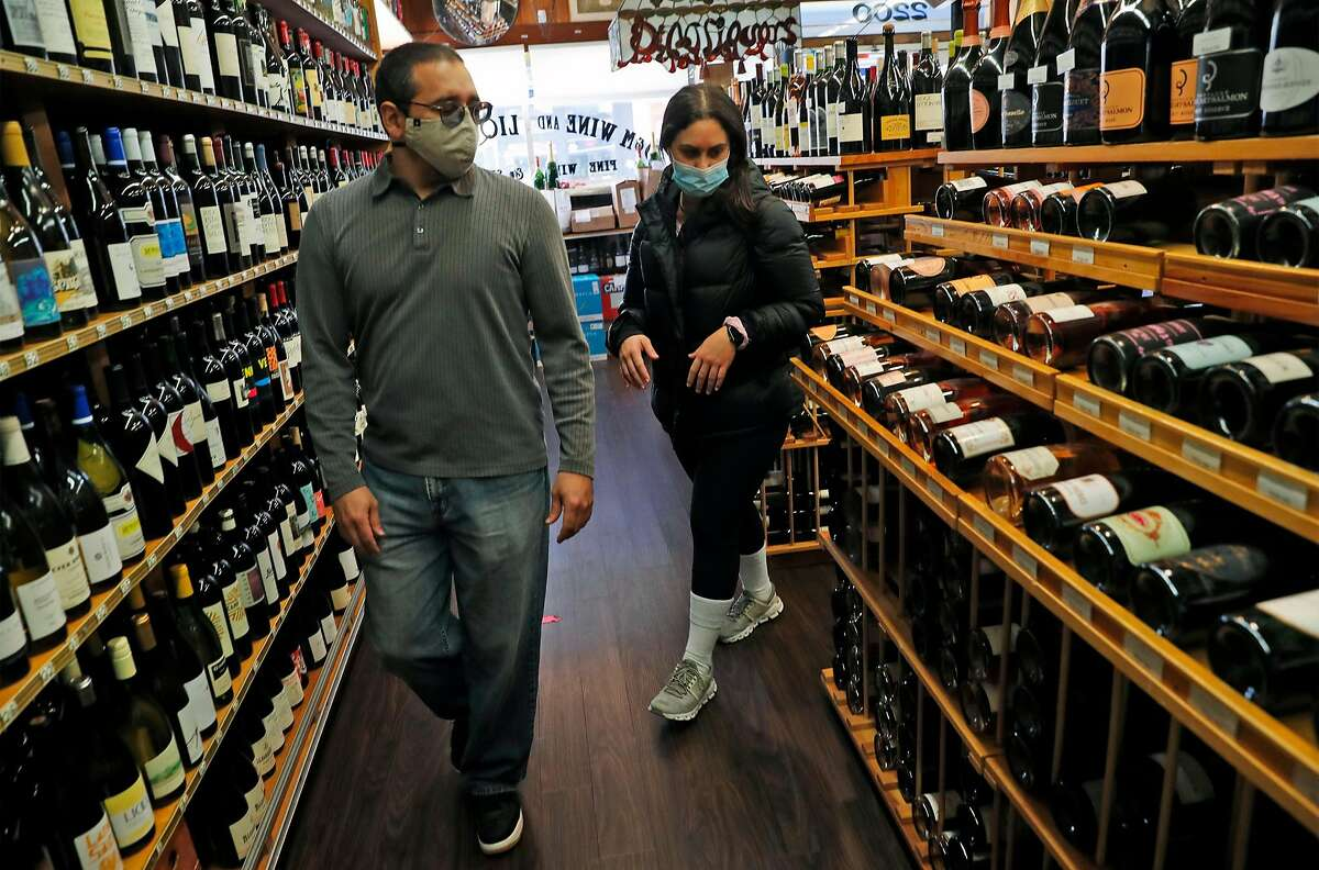 D&M Wine and Liquor's David Gray helps Jessica Hennessey shop for a bottle of champagne for New Years' Eve on Fillmore Street in San Francisco, Calif., on Wednesday, December 30, 2020.
