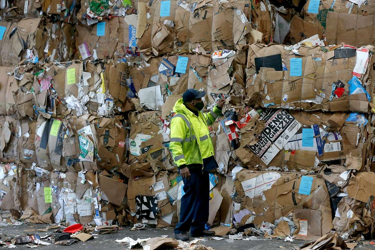 Reggie Cummings inspects bales of cardboard stacked at the Recology recycling facility on Pier 96 in San Francisco.
