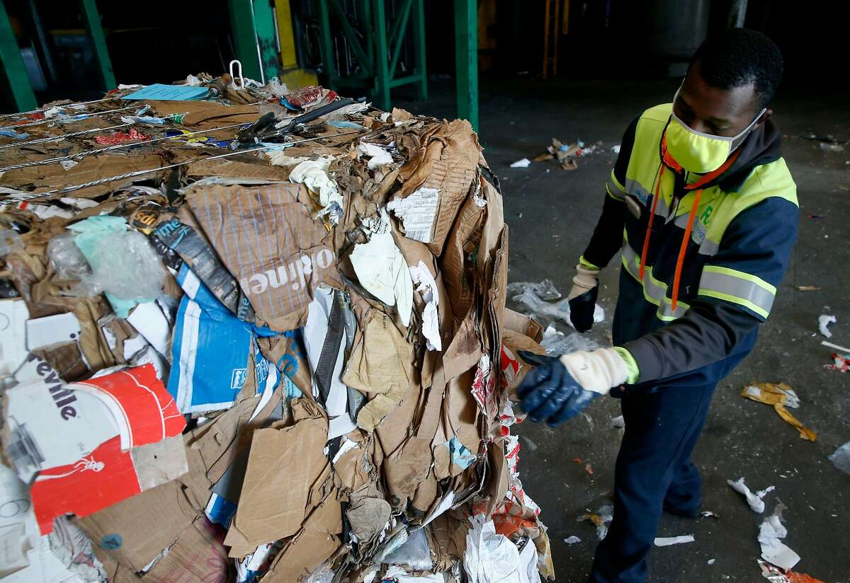 Anthony Babbs readies a bale of flattened cardboard for shipping at the Recology facility on Pier 96. Some cardboard is shipped overseas for processing.