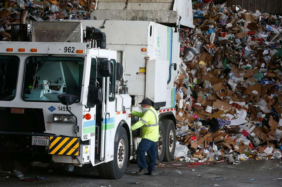 A driver unloads cardboard and other recyclables collected from homes throughout the city at the Recology central recycling warehouse in San Francisco, Dec. 30, 2020.