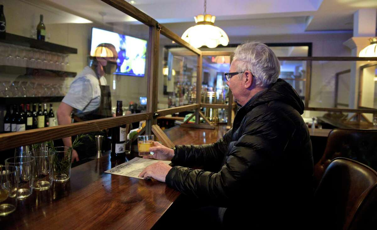 Gus Palmieri of Trumbull orders a drink from bartender Shine Bingham at Good Old Days Pizzeria and Cocktail Den in Newtown on December 30, 2020.
