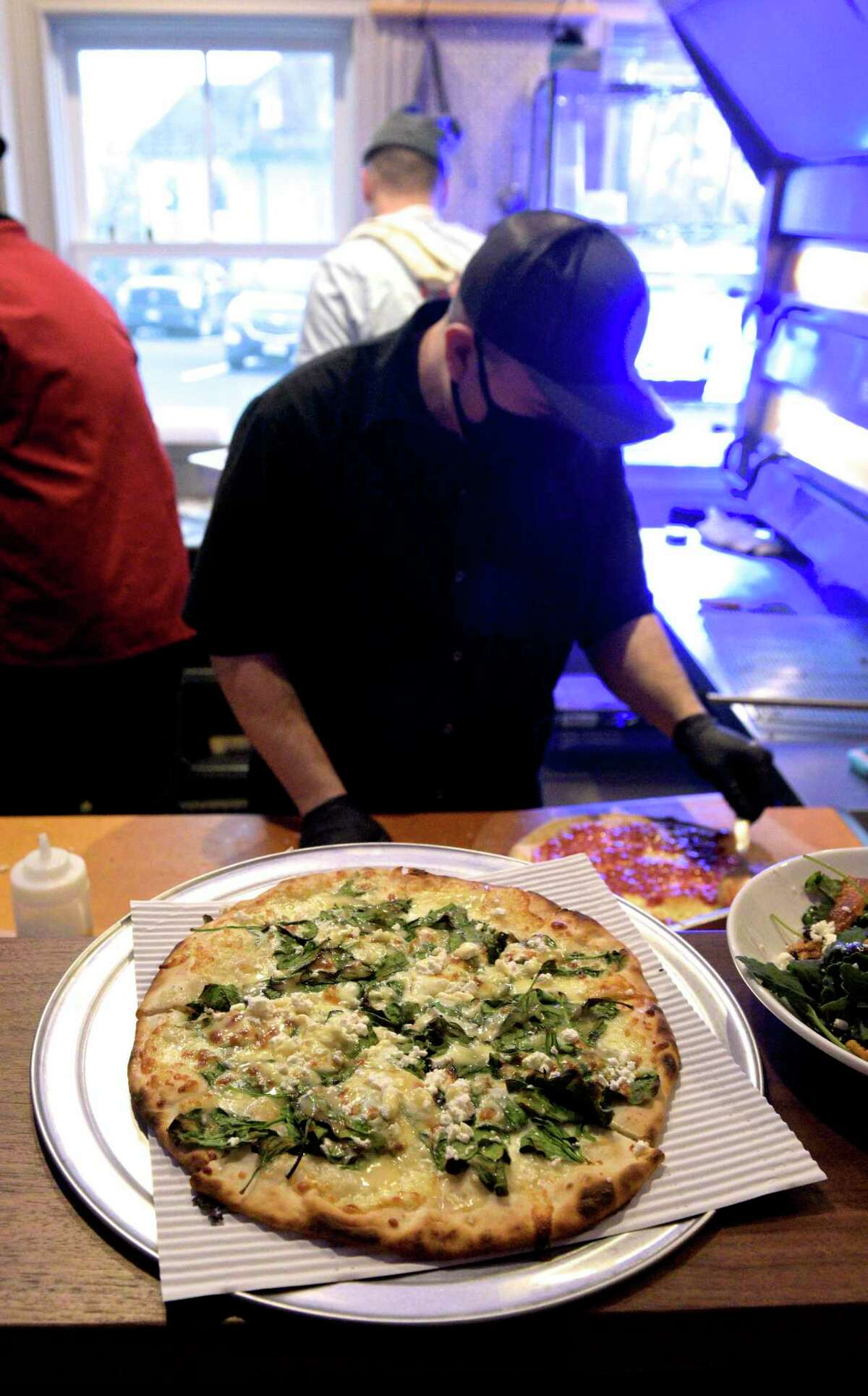A hot pizza ready to be delivered to a table while pizza guy Glen Horton prepares another at Good Old Days Pizzeria and Cocktail Den, in the lower level of Marygold's on Main. The restaurant had its opening night on Wednesday, December 30, 2020, in Newtown. Conn.