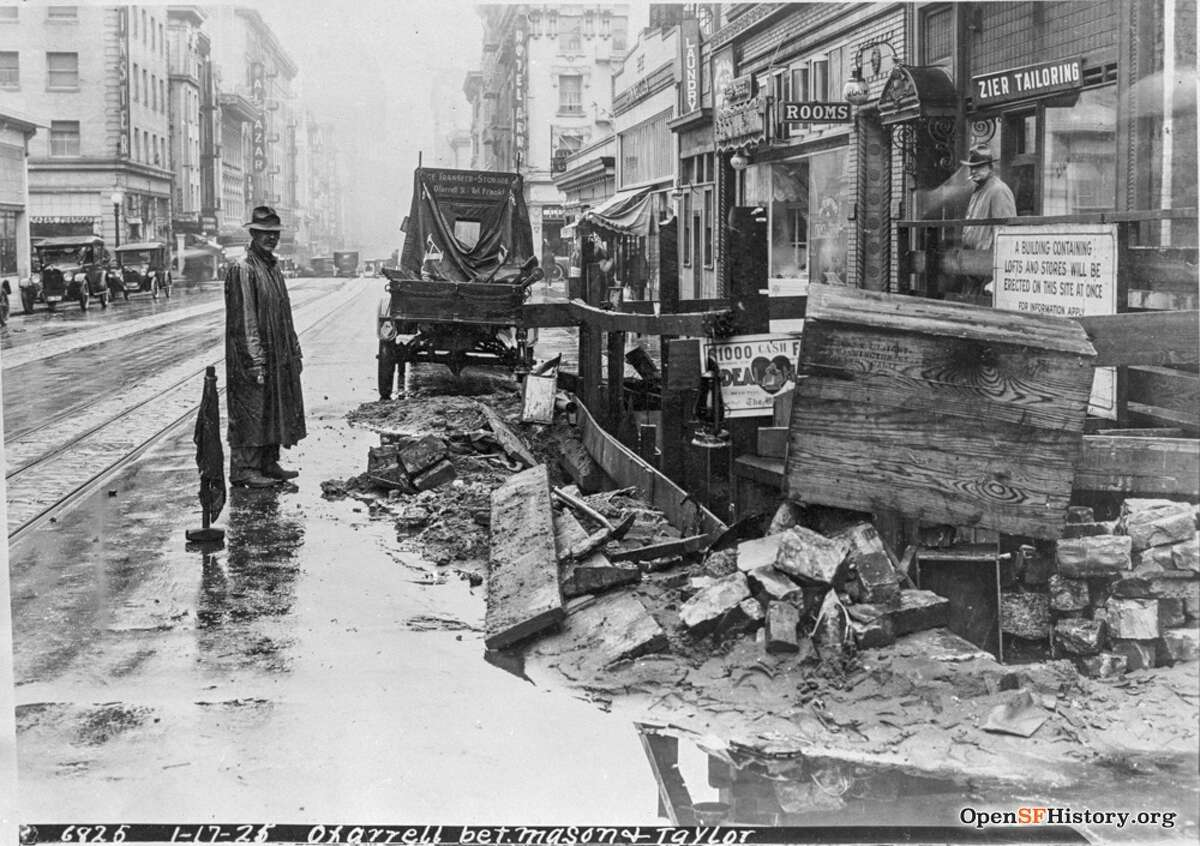 A wet day in the Tenderloin. A man stands by a construction site on O'Farrell and Mason in 1921. The Alcazar Theatre can be seen in distance.