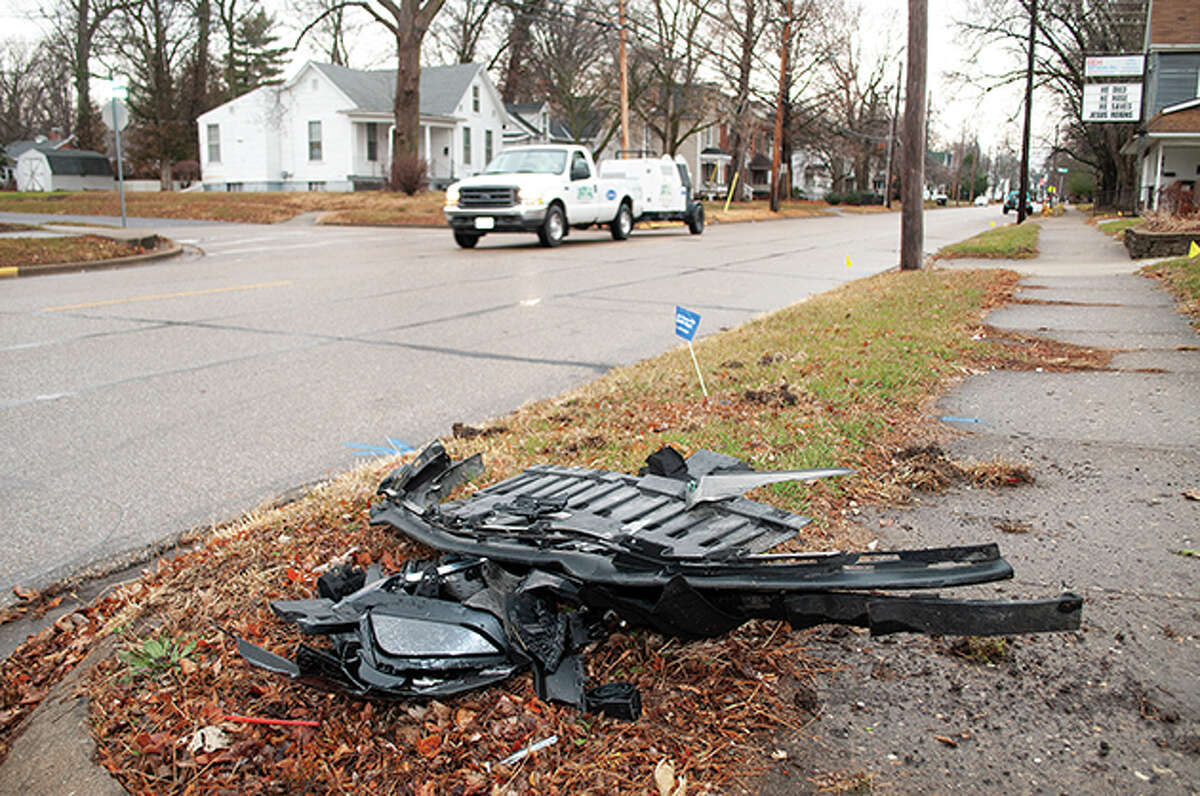 Debris from a car is piled up in a yard after a driver struck a street sign and drove on the sidewalk on the east side of South Diamond Street. Residents of the neighborhood helped clear debris from the street after the driver was apprehended by Jacksonville police.