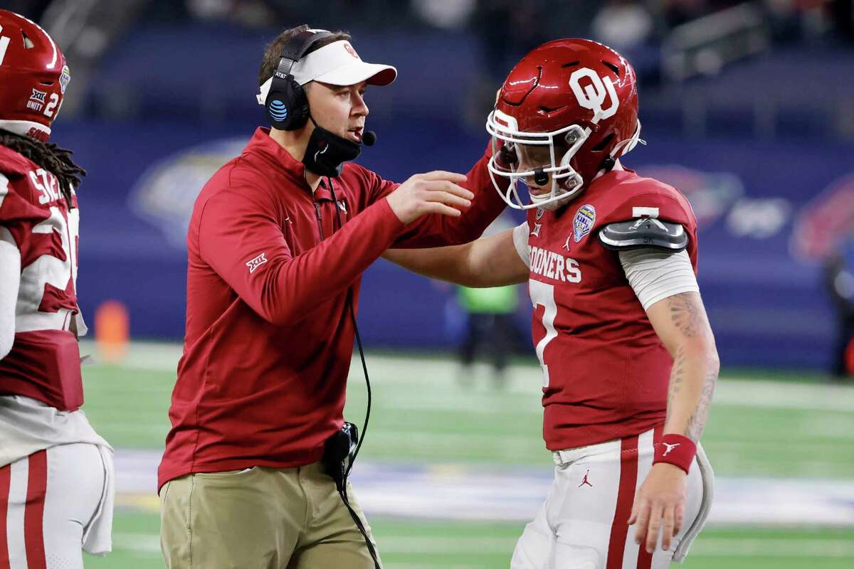 Oklahoma coach Lincoln Riley, left, celebrates with quarterback Spencer Rattler after Rattler ran the ball for a touchdown against Florida in the first half of the Cotton Bowl NCAA college football game in Arlington, Texas, Wednesday, Dec. 30, 2020.