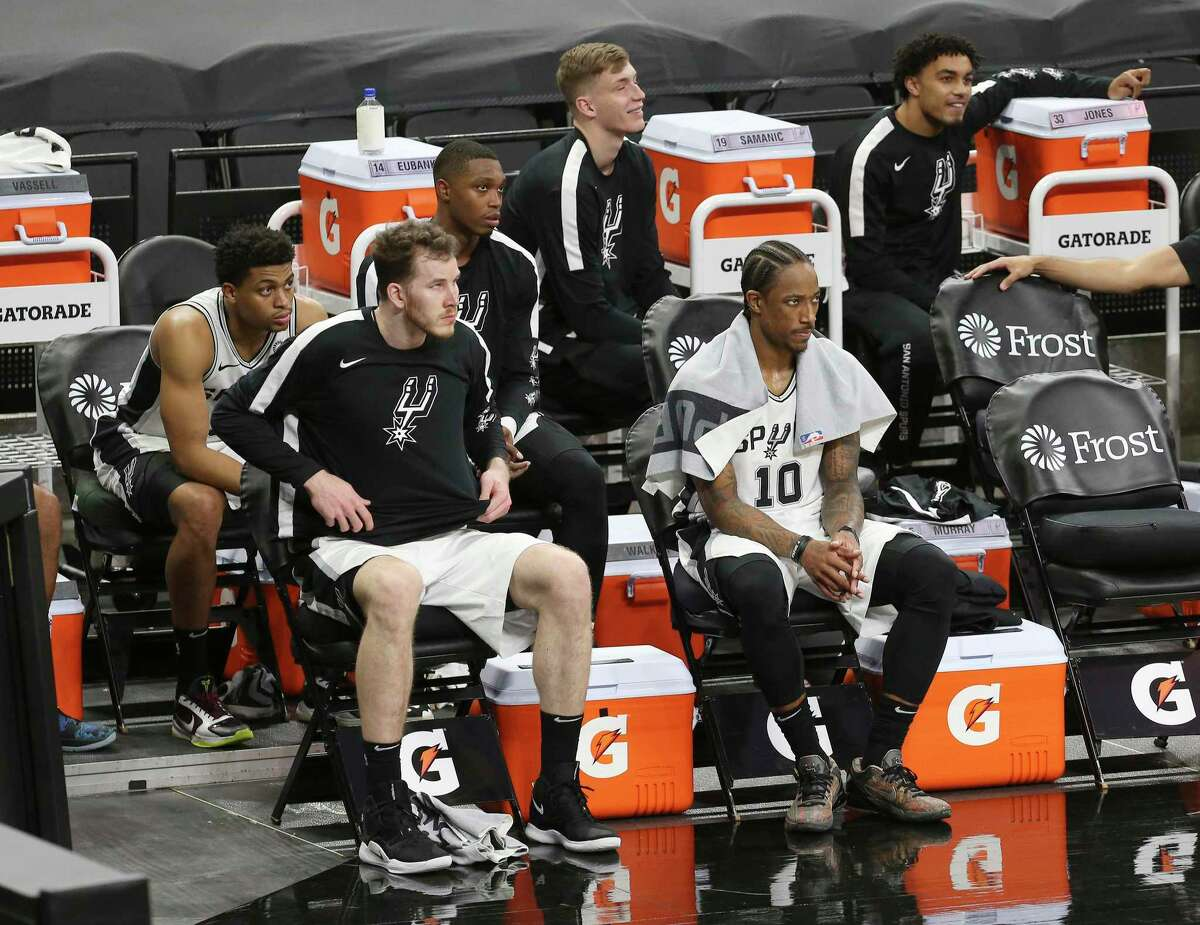 Spurs' Keldon Johnson (03), Jakob Poeltl, Lonnie Walker IV, Luka Samanic, DeMar DeRozan (10) and Tre Jones watch the game from the bench against the Los Angeles Lakers at the AT&T Center on Wednesday, Dec. 30, 2020.