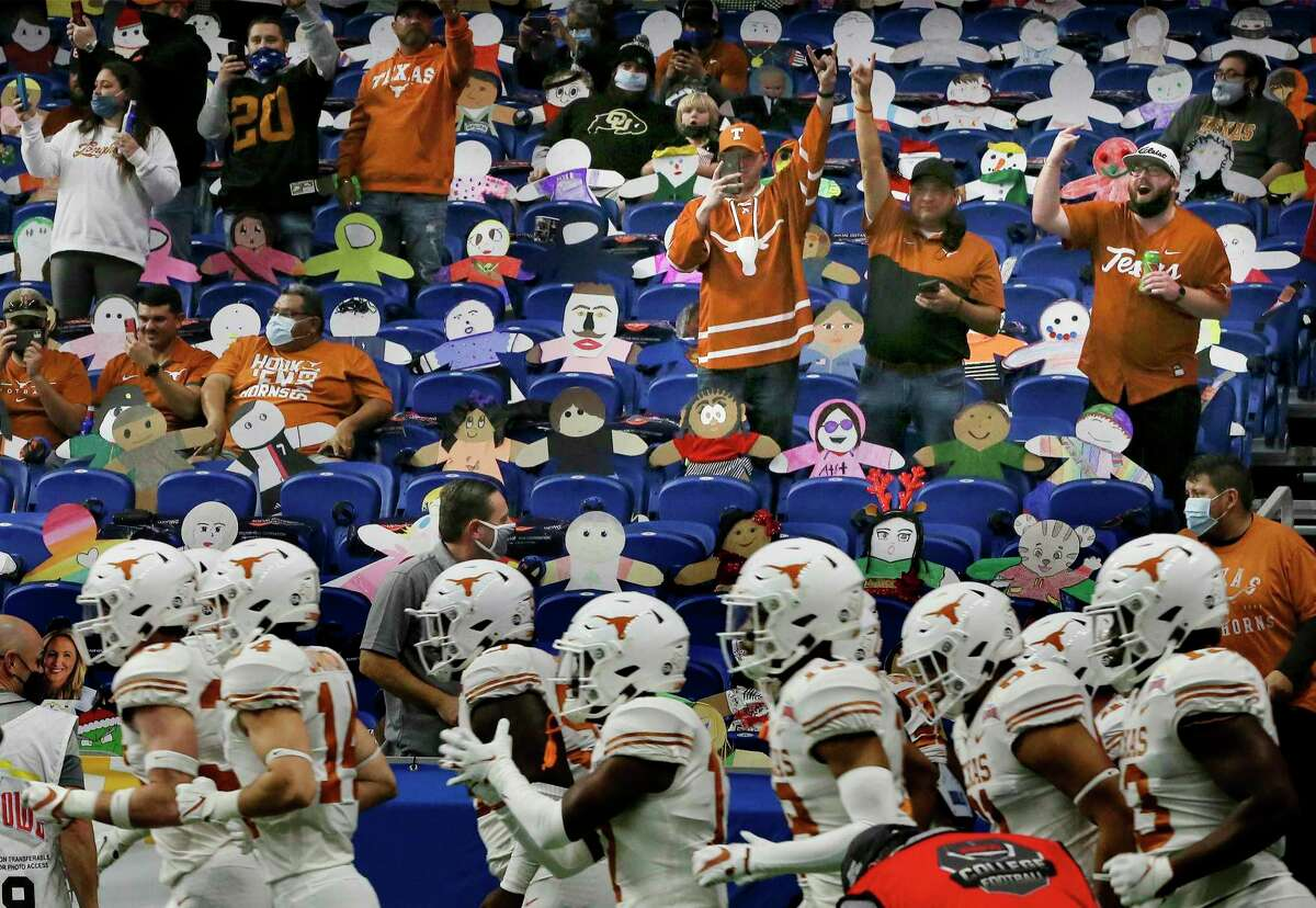 The Texas Longhorns run onto the field for the 2020 Valero Alamo Bowl at the Alamodome. More than a dozen spectators repeatedly refused to wear their masks properly, according to city enforcement data.