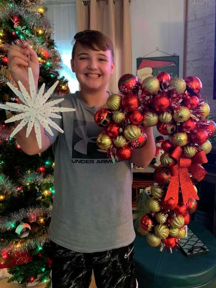 Kaden Moore with a wooden snowflake and candy cane wreath. (Courtesy photo)