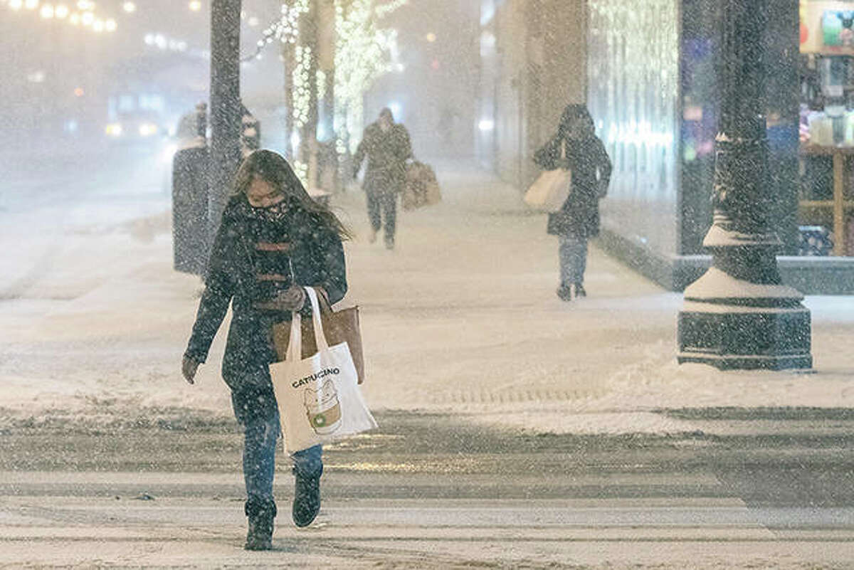 A woman looks at her phone while crossing the street as a strong winter storm made its way into northern Illinois, creating treacherous travel conditions and spurring warnings urging people to stay off the roads. Forecasters said a second storm system is approaching the state and could mean ice and freezing rain for west-central Illinois tonight and snow by this weekend.