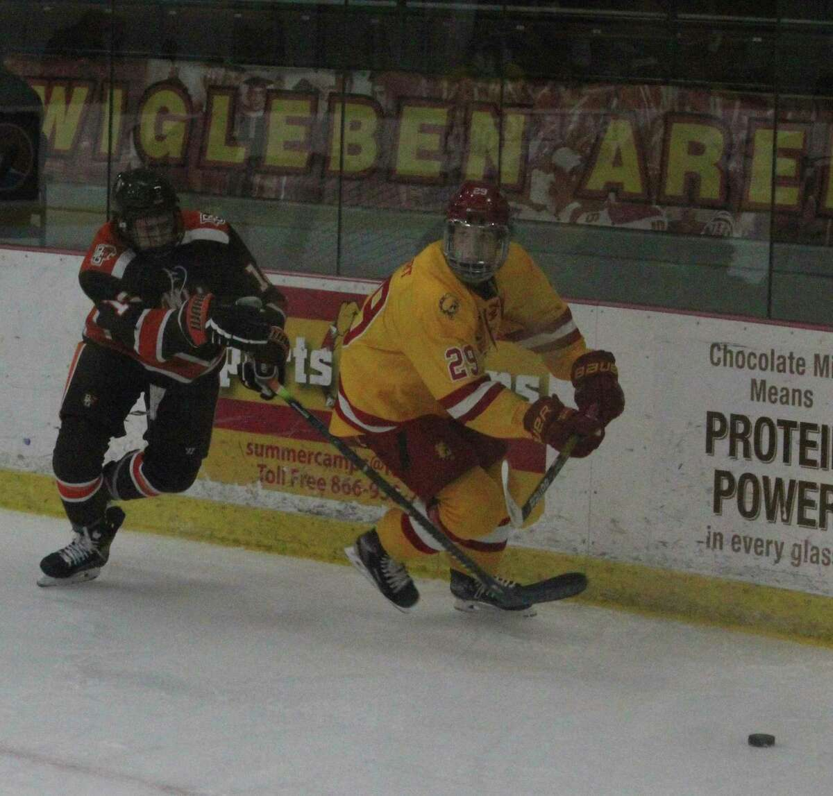 Ferris's Ethan Stewart (right) chases the puck against Bowling Green in a home game earlier this season. (Pioneer photo/John Raffel)