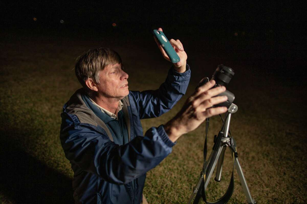 Charles Phillips opens the Orbitrack app on his cellphone and waits for a satellite to move over the horizon to photograph it at a baseball field near his home, Wednesday, Dec. 9, 2020, in Clear Lake. Phillips tracks satellites as a hobby, and sends the data he collected to another member of the SeeSat-L list who maintains a robust catalog of classified satellites.