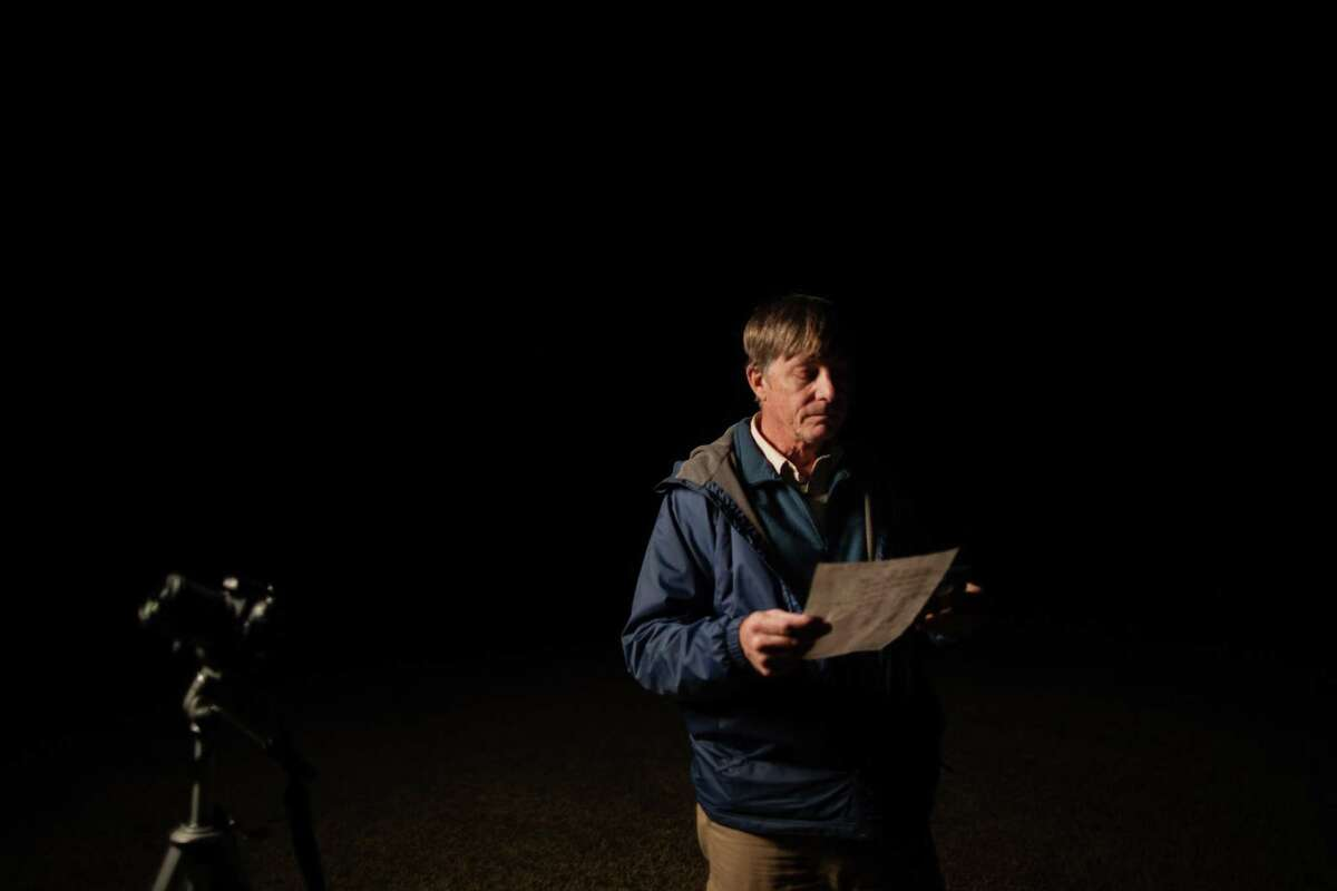 Charles Phillips takes a look at a list of classified satellites he wishes to track using the Orbitrack app and a camera at a baseball field near his home, Wednesday, Dec. 9, 2020, in Clear Lake.