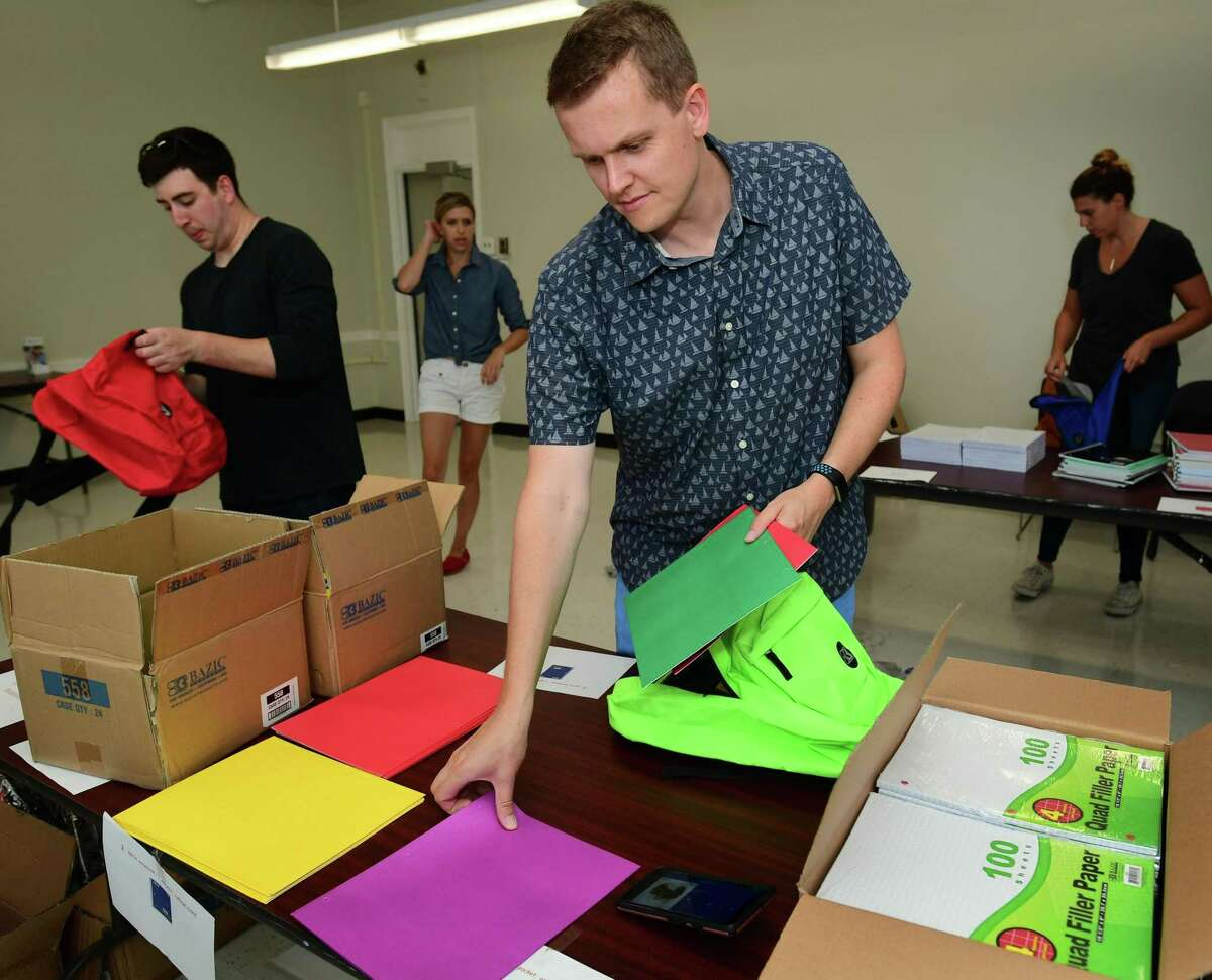 Volunteers from Albourne America, a local alternative investment firm, fill 80 backpacks with school supplies for children in Family & Children's Agency programs Thursday, August 22, 2019, at the FCA facility at Ben Franklin School in Norwalk, Conn.
