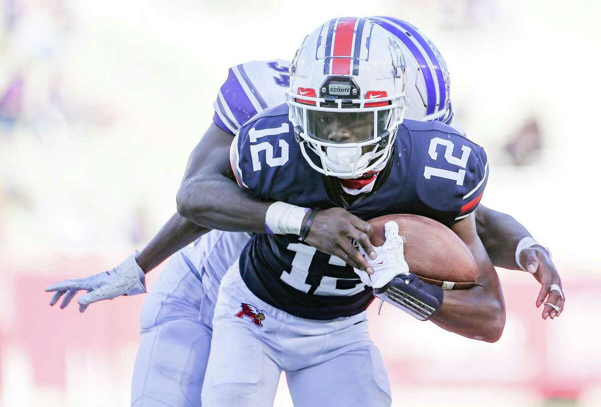 Humble Atascocita wide receiver Keith Wheeler (12) is slowed down by Fort Bend Ridge Point's Frank Osagiede (34) at TDECU Stadium in Houston on Saturday, Dec. 26, 2020. Ridge Point won the game 55-45 for the quarterfinal win.