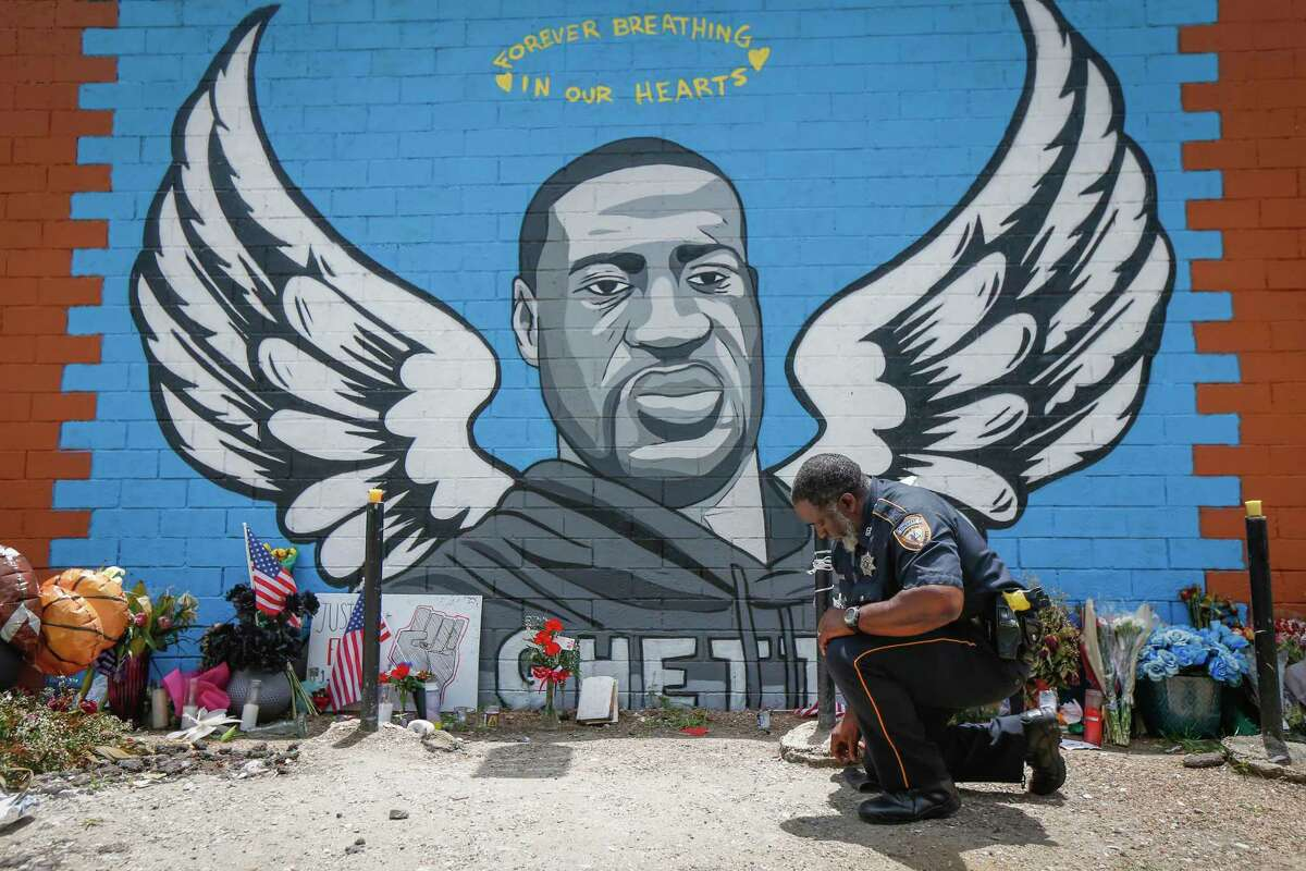 Sheriff Deputy Anthony Glenn paid his respects to George Floyd in front mural made in his honor outside the Scott Food Mart corner store in Houston's Third Ward. Monday, June 8, 2020, in Houston.