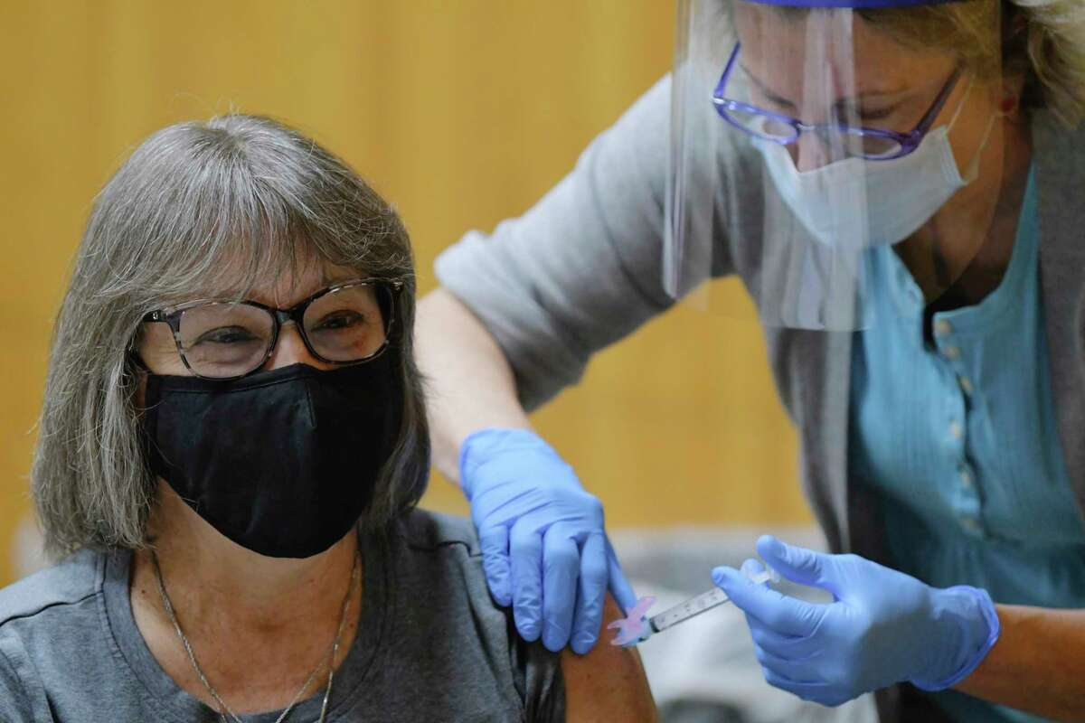 Adele Cramer, left, a nurse at Living Resources, receives the first dose of the Moderna Covid-19 vaccine from Physician assistant Marjorie Schwab at a Covid-19 vaccination clinic at the Schenectady County Public Library on Thursday, Dec. 31, 2020, in Schenectady, N.Y. Schwab is a volunteer with the Schenectady County Medical Reserve Corps. (Paul Buckowski/Times Union)