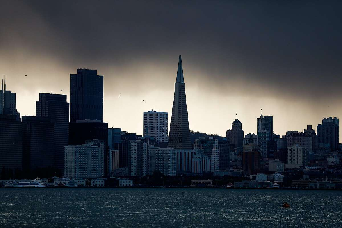 The San Francisco skyline is seen covered in dark clouds during a rainstorm at Treasure Island on Sunday, Nov. 8, 2020 in San Francisco, California.