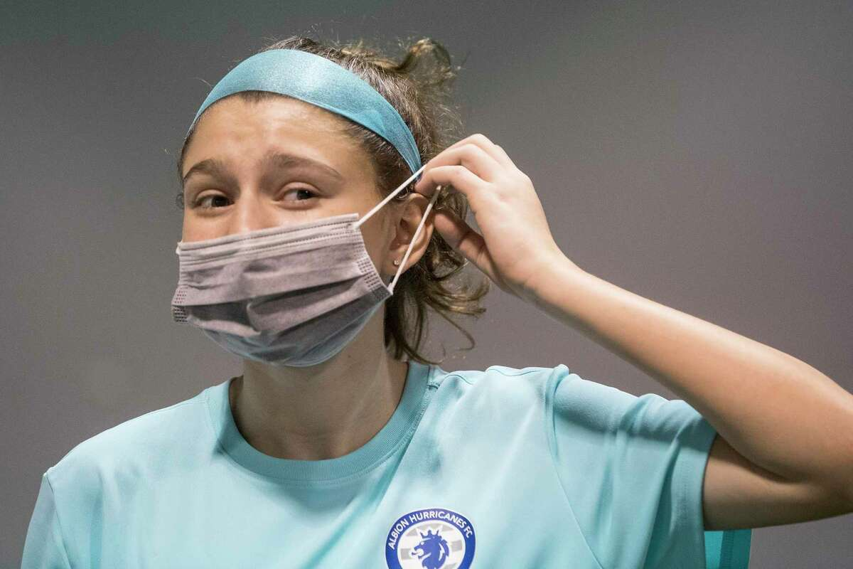 """Soccer player Kira Pevow, 14, puts on her mask after working out at Houston Center for Soccer Tuesday, Dec. 22, 2020 in Houston. After returning to the soccer pitch, Pevow knew something was still wrong. A couple weeks after she thought she'd gotten over COVID-19, her first week back at soccer practice. An elite player usually in top condition, she couldn't run as fast and her stamina wasn't the same. """"It was as if the gasoline tank was empty and the engine was operating on fumes,"""" she said."""