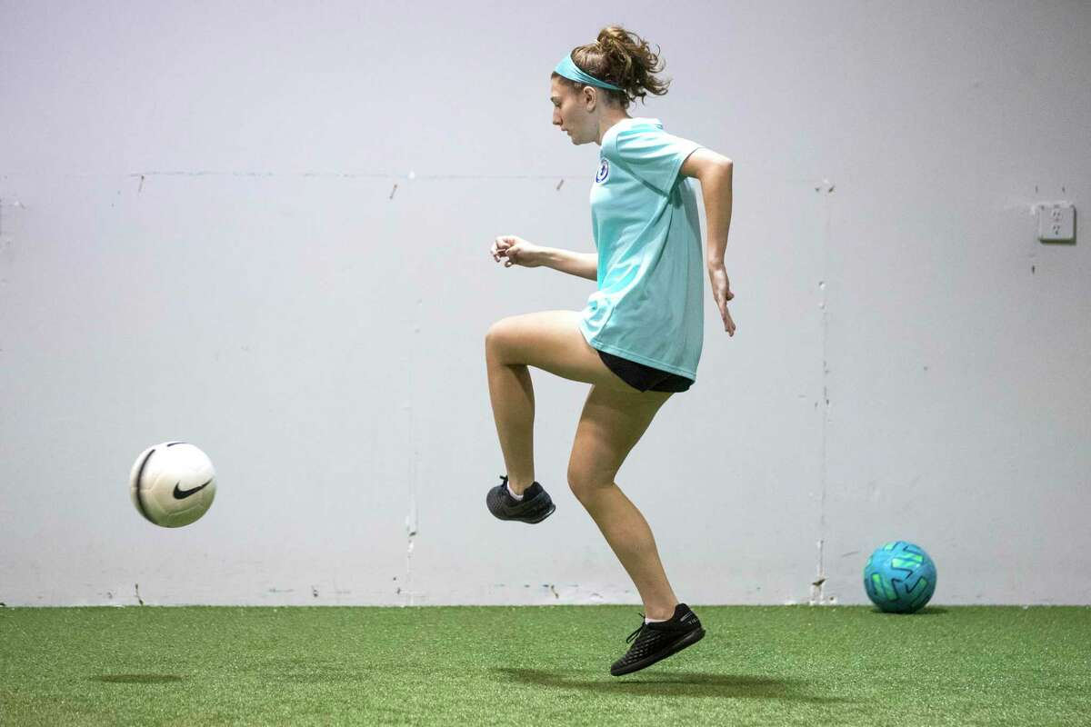 """Soccer player Kira Pevow, 14, works out at Houston Center for Soccer Tuesday, Dec. 22, 2020 in Houston. Pevow got COVID-19 during the summer, thought she would recover quickly but instead had lingering heart-related problems, a little known complication in some kids. After returning to the soccer pitch, she knew something was still wrong. A couple weeks after she thought she'd gotten over COVID-19, her first week back at soccer practice. She couldn't run as fast and her stamina wasn't the same. """"It was as if the gasoline tank was empty and the engine was operating on fumes,"""" she said."""