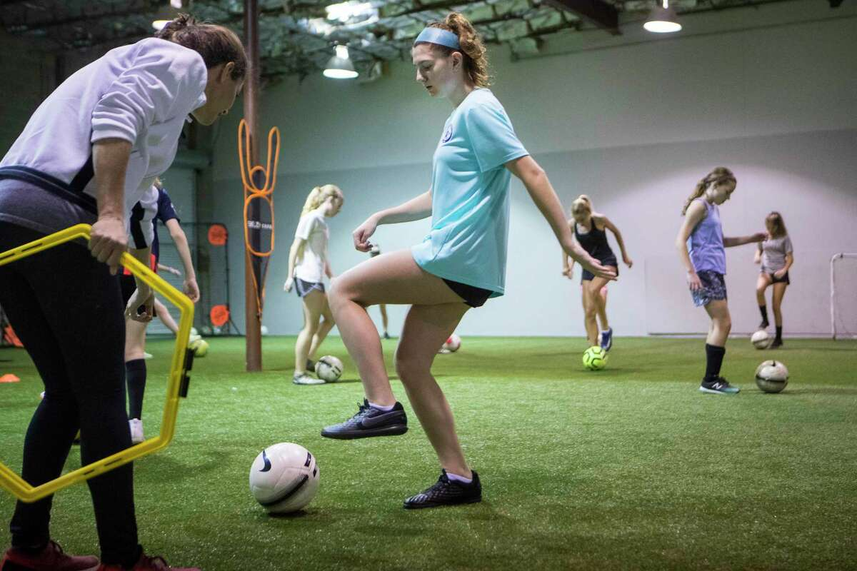 """Soccer player Kira Pevow, 14, works out with trainer Jacy Giambi at Houston Center for Soccer Tuesday, Dec. 22, 2020 in Houston. Pevow got COVID-19 during the summer, thought she would recover quickly but instead had lingering heart-related problems, a little known complication in some kids. After returning to the soccer pitch, she knew something was still wrong. A couple weeks after she thought she'd gotten over COVID-19, her first week back at soccer practice. She couldn't run as fast and her stamina wasn't the same. """"It was as if the gasoline tank was empty and the engine was operating on fumes,"""" she said."""