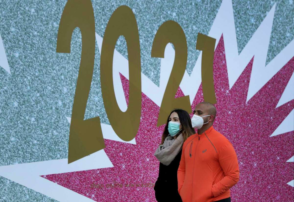 People wear face masks as they walk past the 'KaDeWe' department store in Berlin, Germany, Thursday, Dec. 31, 2020. Germany is entering 2021 in a lockdown that appears certain to be extended beyond its current Jan. 10 end date, with new coronavirus cases and deaths related to COVID-19 remaining at worryingly high levels. The country has recorded well over 1.6 million cases so far, including more than 32,000 deaths. (AP Photo/Michael Sohn)