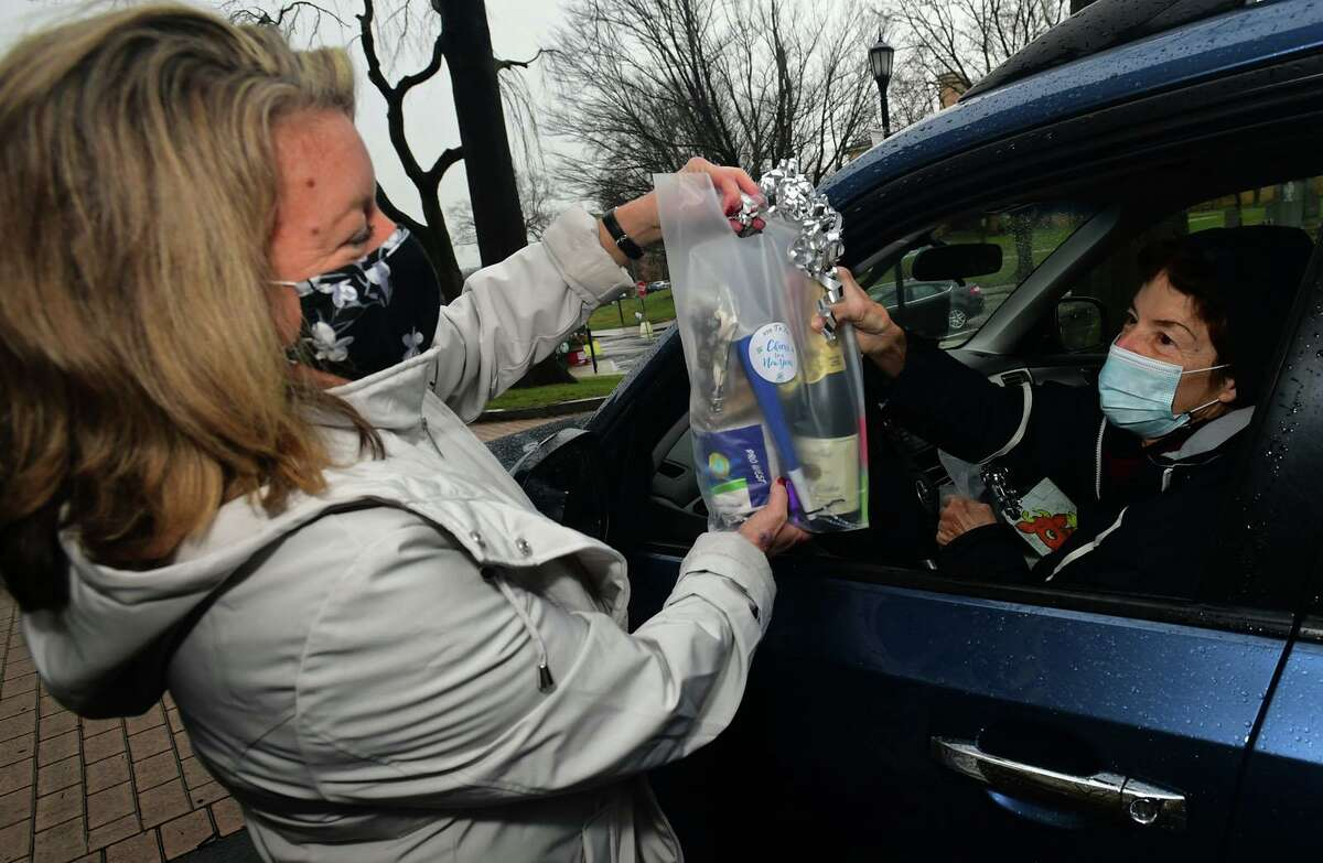 Deana Salerno of The Greenwich Senior Center hands a bag to Carolyn Servidio as the Center and the Commission on Aging hold a free New Year's Eve gift giveaway drive-thru Thursday, December 31, 2020, at the Senior Center in Greenwich, Conn.