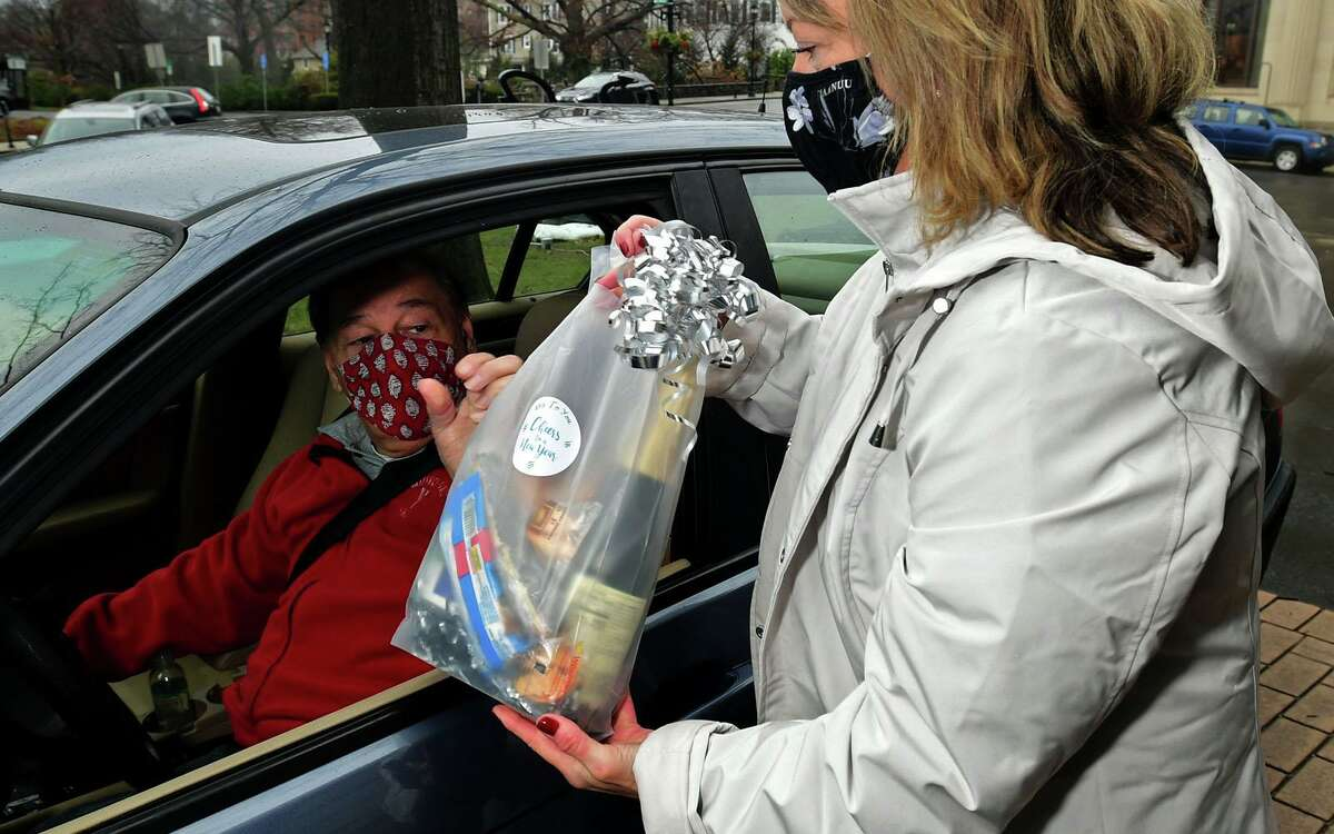 Deana Salerno of The Greenwich Senior Center hands a bag to Frank Rota as the Center and the Commission on Aging hold a free New Year's Eve gift giveaway drive-thru Thursday, December 31, 2020, at the Senior Center in Greenwich, Conn.