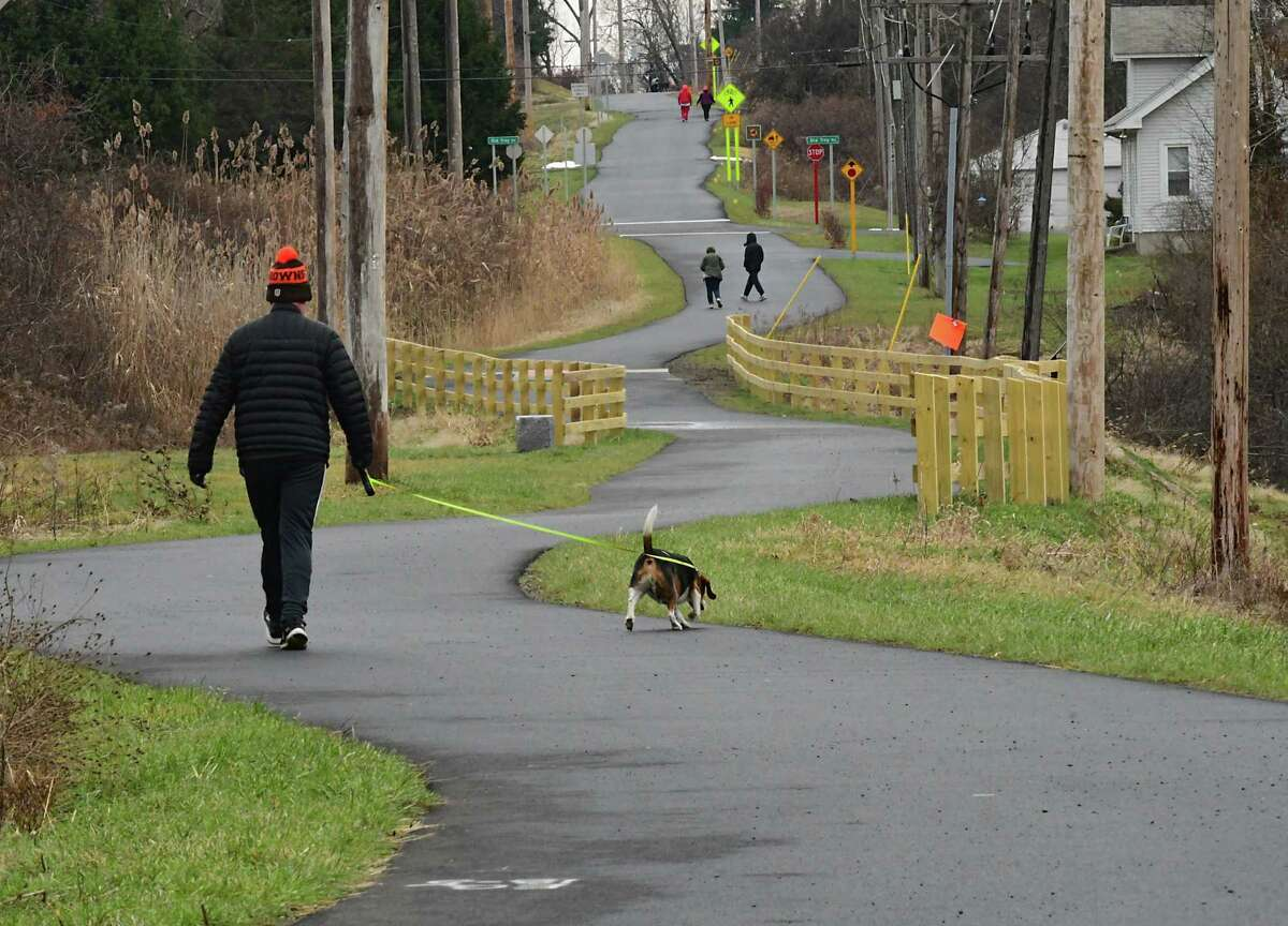 Lew Dubuque of East Greenbush walks his dog Buddy on the new Empire State Trail on Thursday, Dec. 31, 2020 in East Greenbush, N.Y. New York State Governor Andrew Cuomo announced that today the trail is officially completed. The 750-mile multi-use trail runs from Manhattan north to the Canadian border in Rouses Point, near the northern tip of Lake Champlain, and also from Buffalo to Albany. (Lori Van Buren/Times Union)