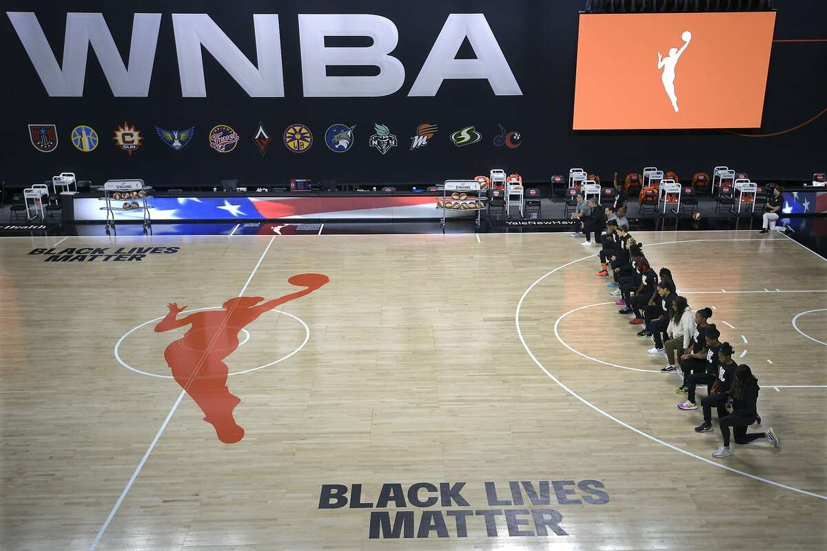 FILE - In this Aug. 30, 2020, file photo, members of the Connecticut Sun team kneel during the playing of the national anthem before a WNBA basketball game against the Washington Mystics in Bradenton, Fla.. (AP Photo/Phelan M. Ebenhack, File)