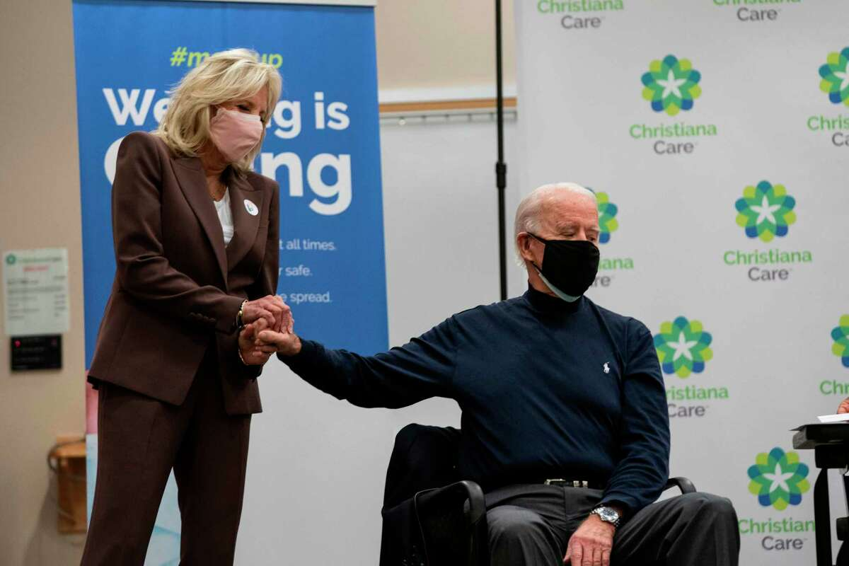 Jill Biden holds the hand of President-elect Joe Biden after he recieved a COVID-19 vaccination on Dec. 21. Jill Biden might not be a medical doctor, but she has earned her title.