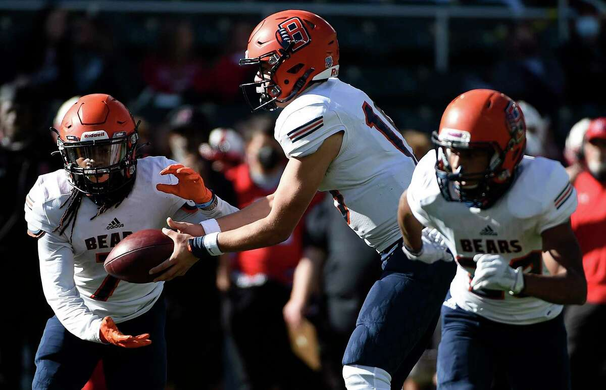 Bridgeland quarterback Conner Weigman, center, hands off the ball to wide receiver Atrevion Hunter, left, during the first half of a 6A Division II Region II regional semi-final high school football playoff game against Rockwall-Heath, Saturday, Dec. 26, 2020, in Waco, TX.
