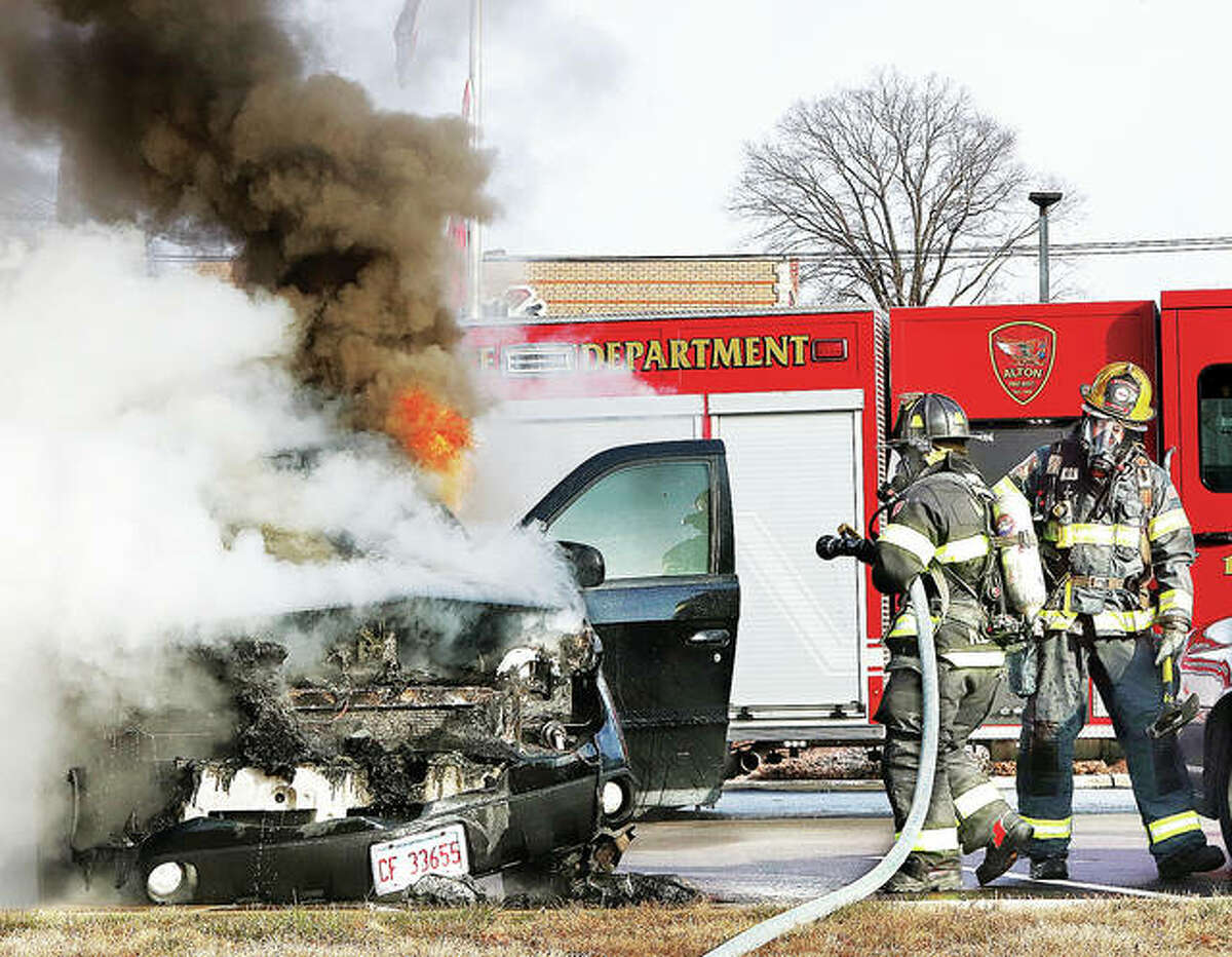 Alton firefighters move in to extinguish flames inside a Pontiac Aztek Thursday on the parking lot of the downtown Alton McDonalds restaurant. No explanation was immediately available on the cause of the fire but it strted in the engine compartment and spread to the interior of the vehicle, which was a total loss. No injuries were reported and there was no damage to the restaurant.