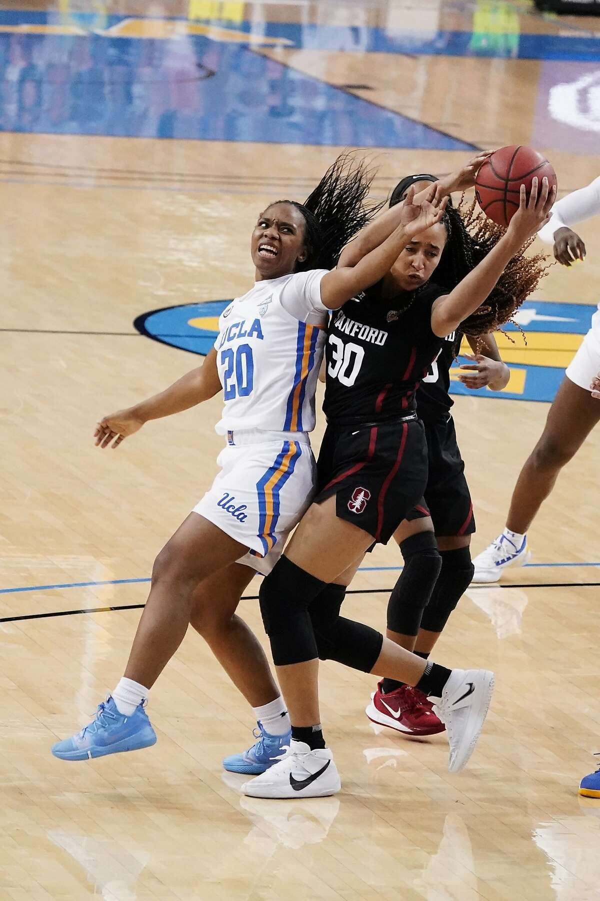 Stanford guard Haley Jones (30) works for the ball against UCLA guard Charisma Osborne (20) during the second half of an NCAA college basketball game Monday, Dec. 21, 2020, in Los Angeles. (AP Photo/Marcio Jose Sanchez)