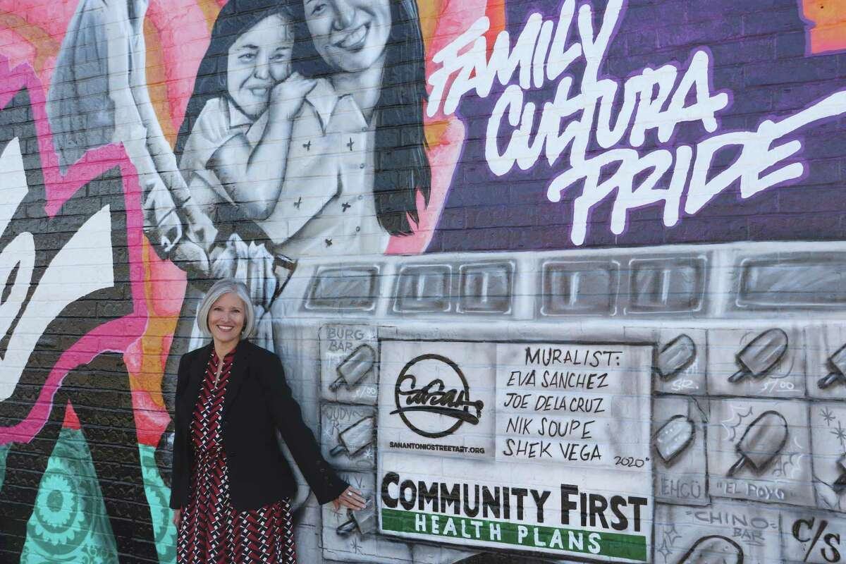 """Theresa Scepanski, president and CEO of Community First Health Plans, poses beside """"We Love Our Southside."""""""
