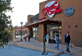 Customers walk by the entrance at the Guitar Center store in Emeryville, Calif., on Wednesday, December 30, 2020. Guitar Center is the latest large retailer to go bankrupt this year, and continues to sell and accept gift cards as it works to reorganize and emerge from its financial woes.