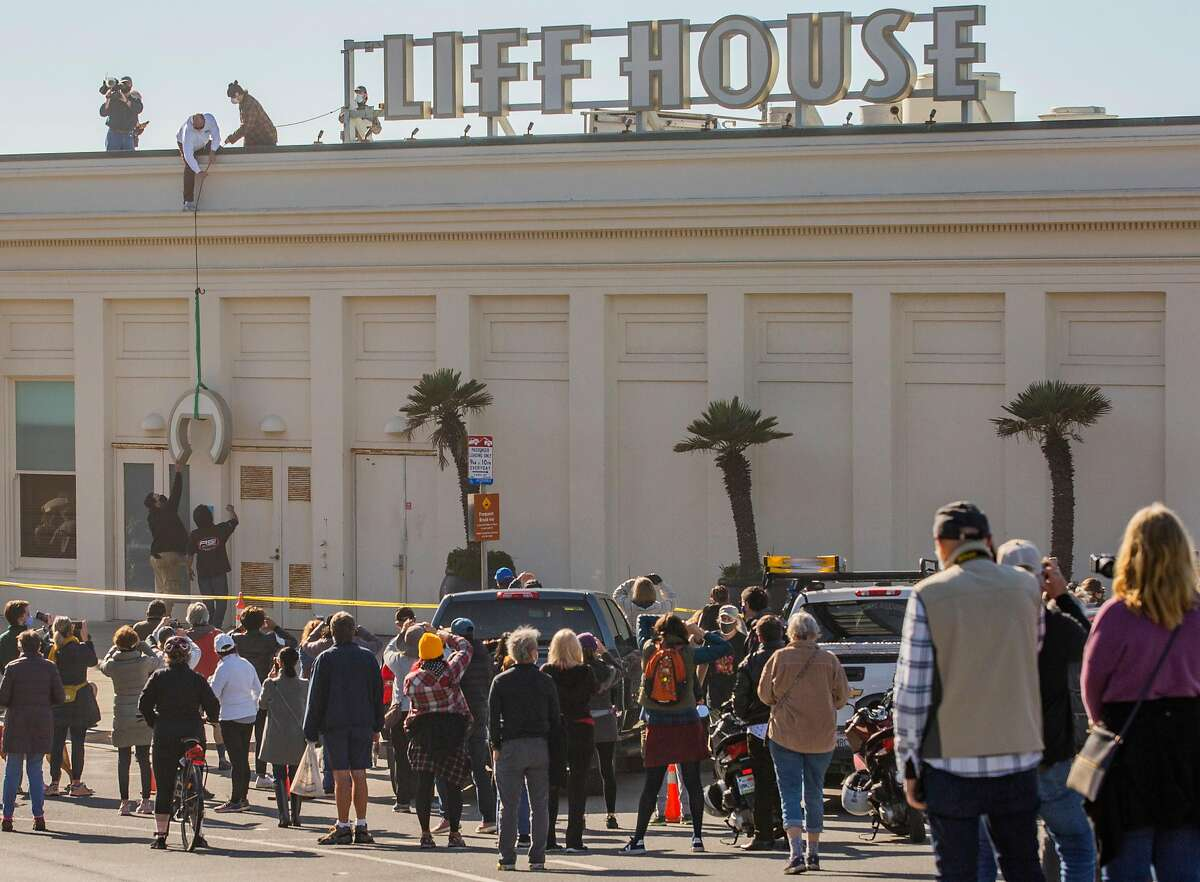 A crowd of nostalgic longtime customers and onlookers gathered to watch the sign for the Cliff House, a trademarked name, taken down.