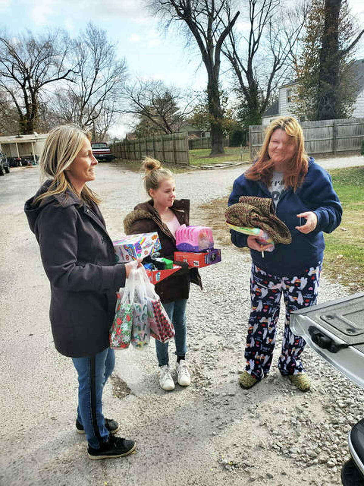 Families receive gifts and personal items from Riverbend Family Ministries volunteers Dave Thomason, owner and founder of River's Edge Entertainment, John Fuller, Paula Rhoades and 8-year-old Jamie during the week of Christmas.