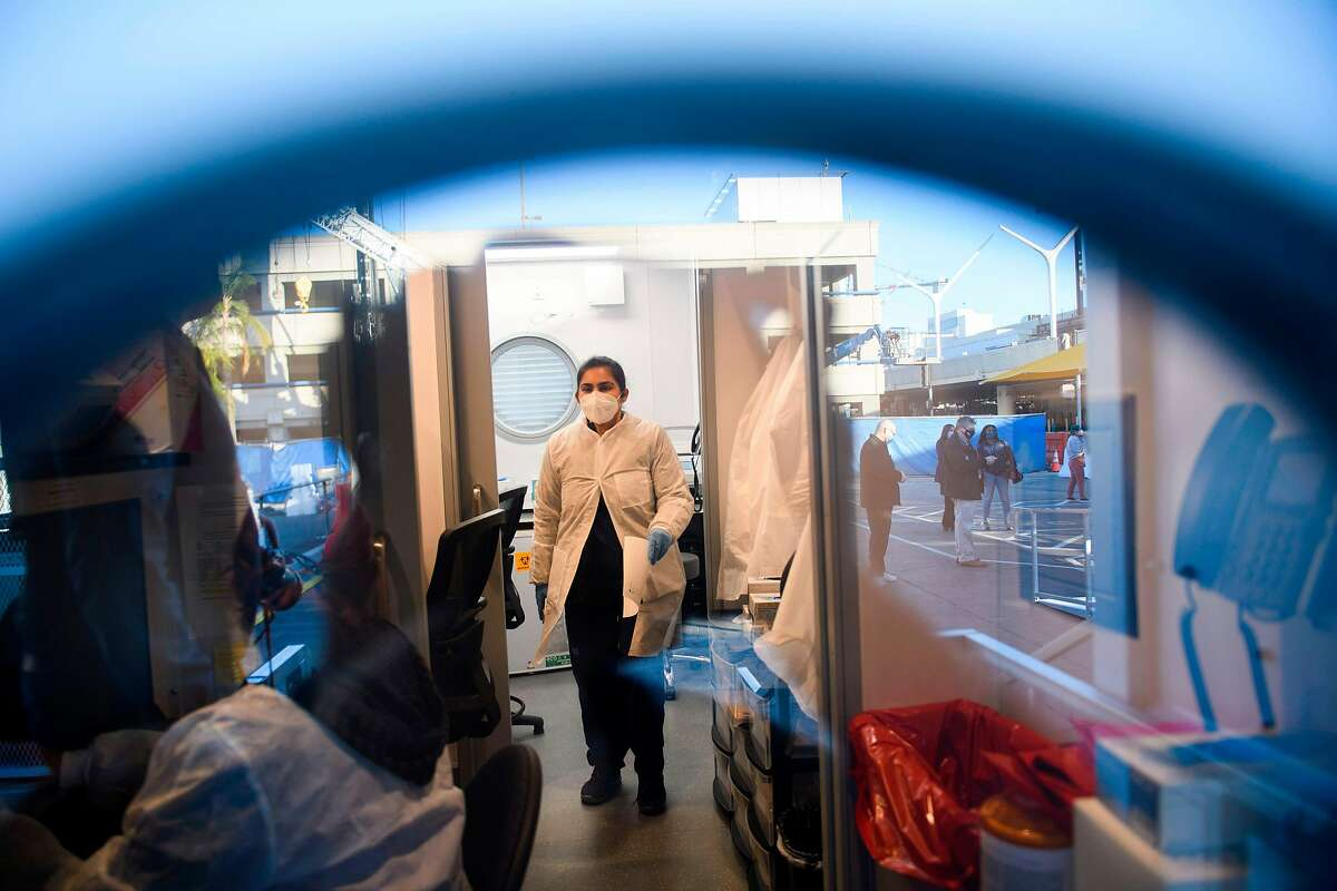 Staff members process tests at an on-site COVID-19 rapid testing laboratory at Los Angeles International Airport.