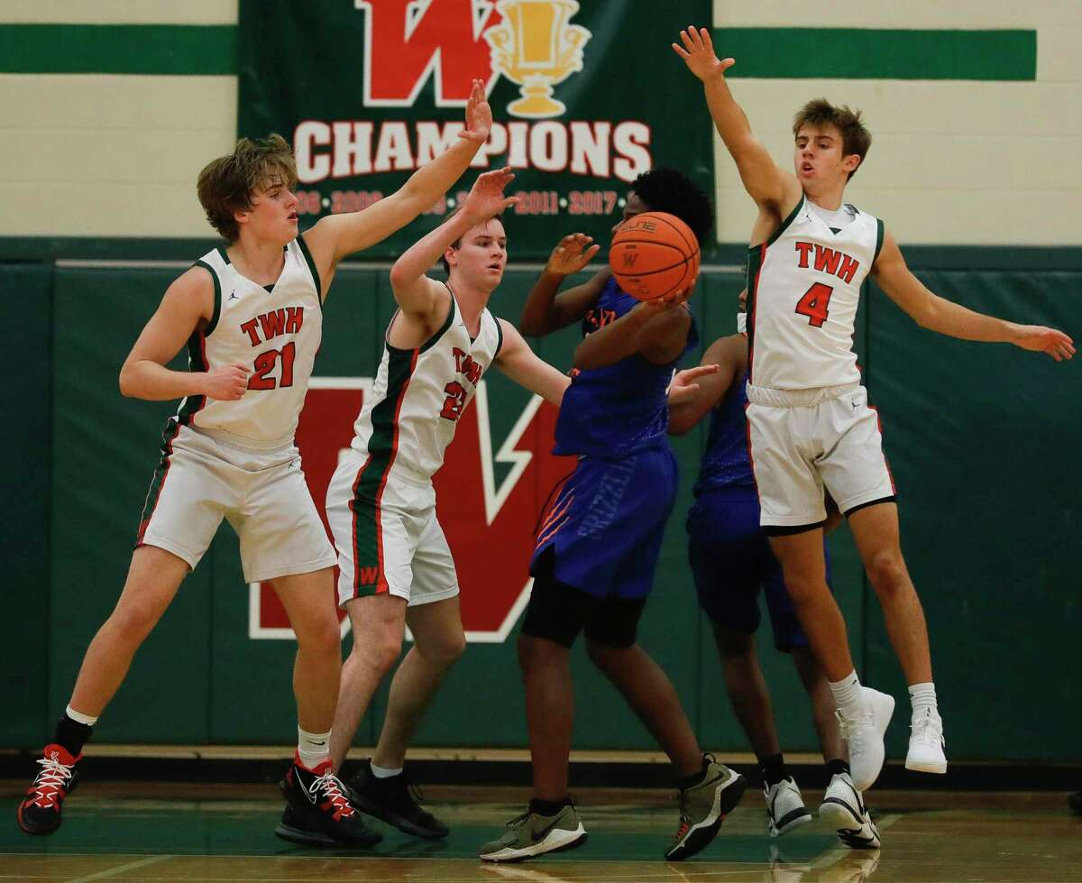 Grand Oaks guard Eli Augustine (33) looks to pass as The Woodlands forward Kylan Williams (21), center Brock Luechtefeld (22) and guard Cade Moore (4) collapse during the first quarter of a District 13-6A high school basketball game at The Woodlands High School, Thursday, Dec. 31, 2020, in The Woodlands.