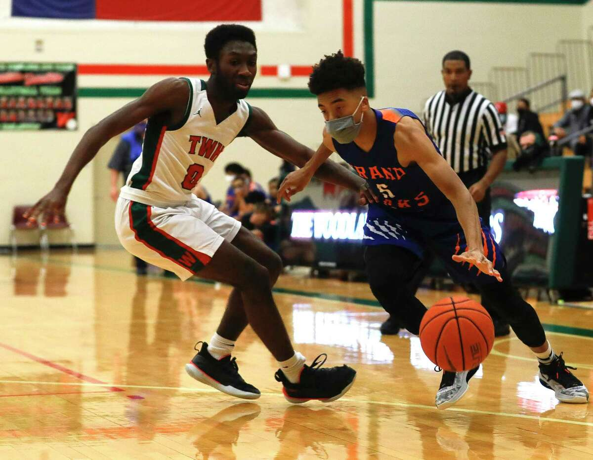 Grand Oaks guard Chamberlain Newman (5) drives past The Woodlands guard David Omokwale (0) during the first quarter of a District 13-6A high school basketball game at The Woodlands High School, Thursday, Dec. 31, 2020, in The Woodlands.