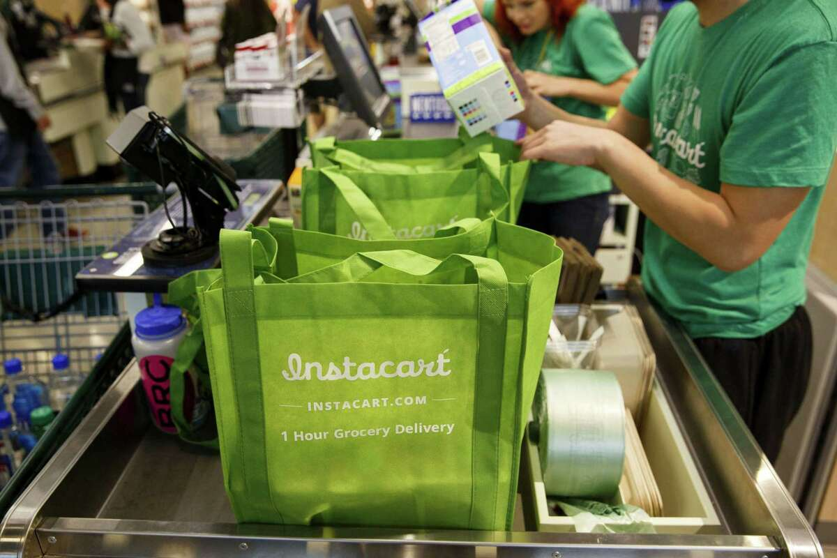 Instacart employees fulfill orders for delivery at a Whole Foods Market in Los Angeles. Instacart The grocery delivery company will be issuing a $25 stipend to all shift leads, in-store shoppers and full-service shoppers who receive their COVID-19 vaccine after Feb. 1.