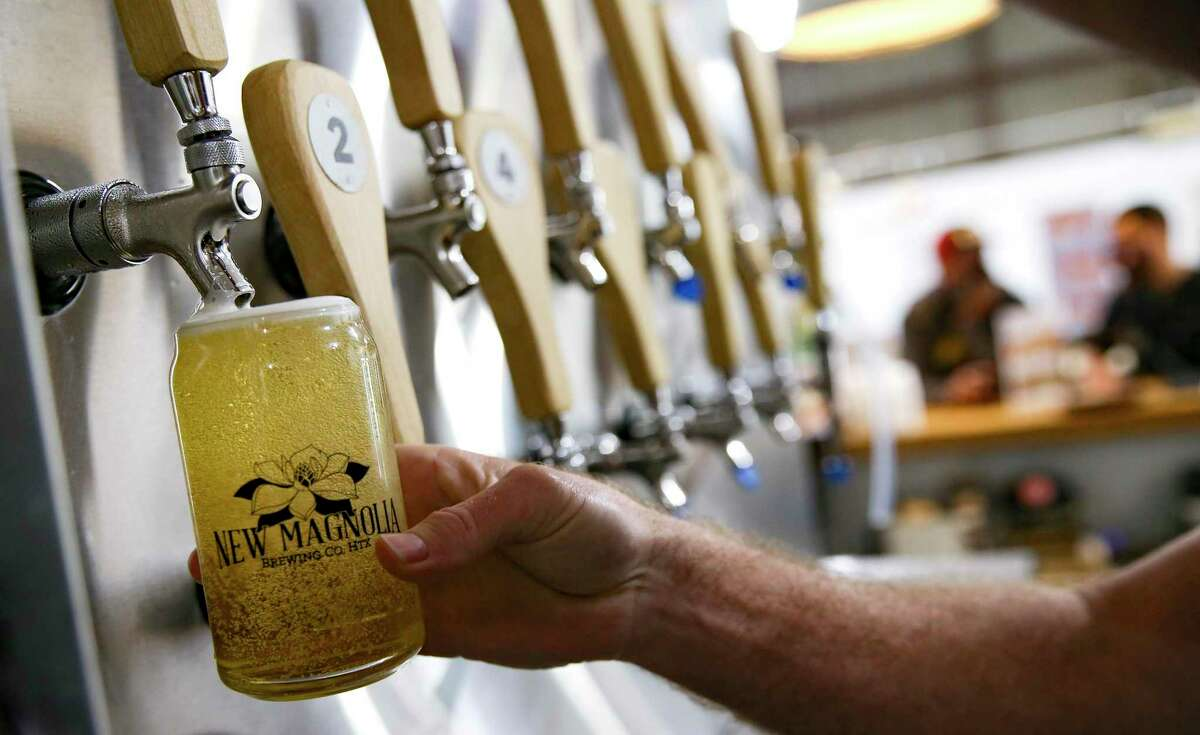 Customers purchase a glass when they get their first beer at New Magnolia Brewing in Houston on Tuesday, Oct. 27, 2020. The brewery has begun offering merchandise and food options in order to qualify as a restaurant and be able to stay open.