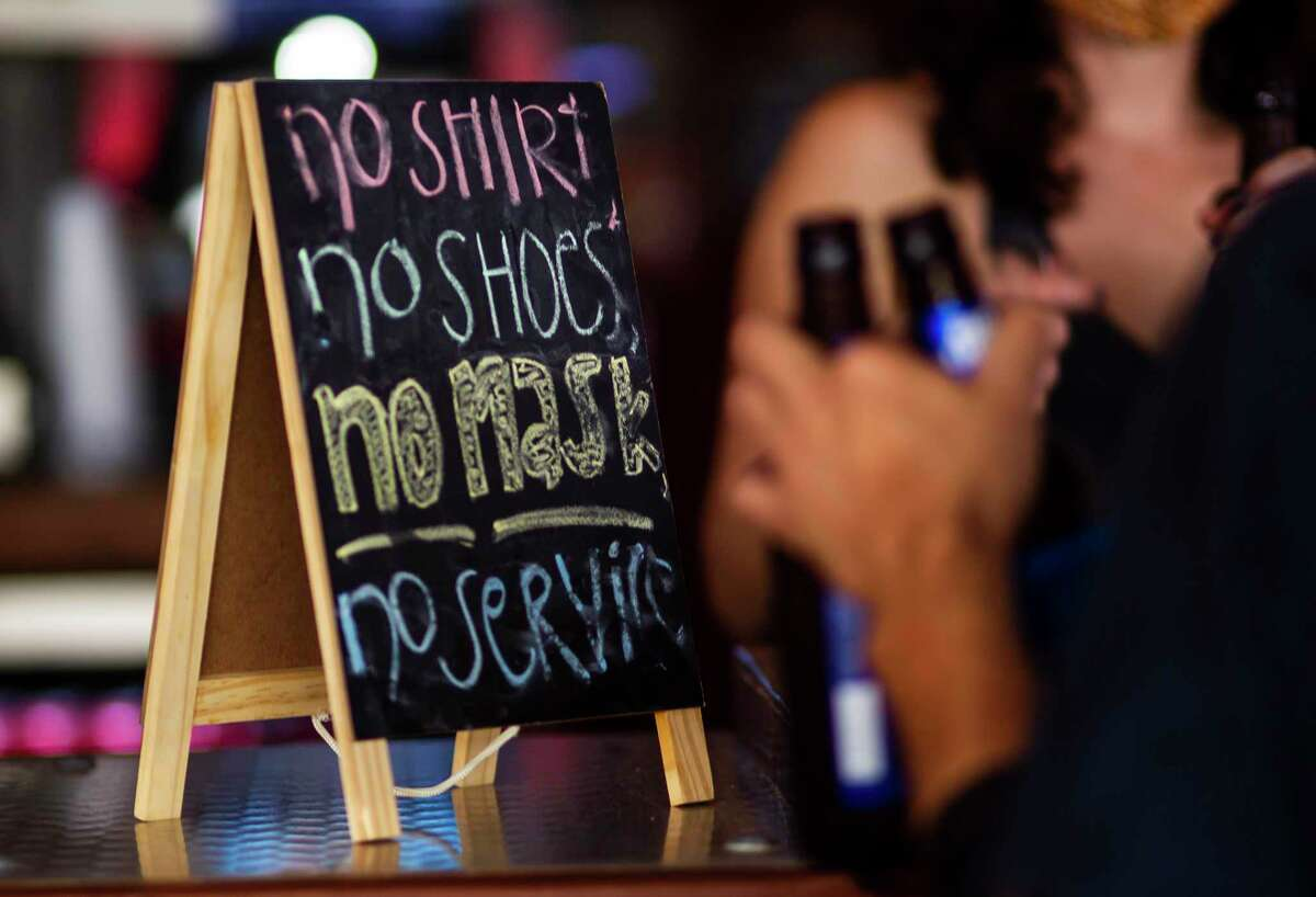 A sign on the bar at the West Alabama Ice House reminds patrons that they need a mask to be served, Saturday, Oct. 3, 2020, in Houston.