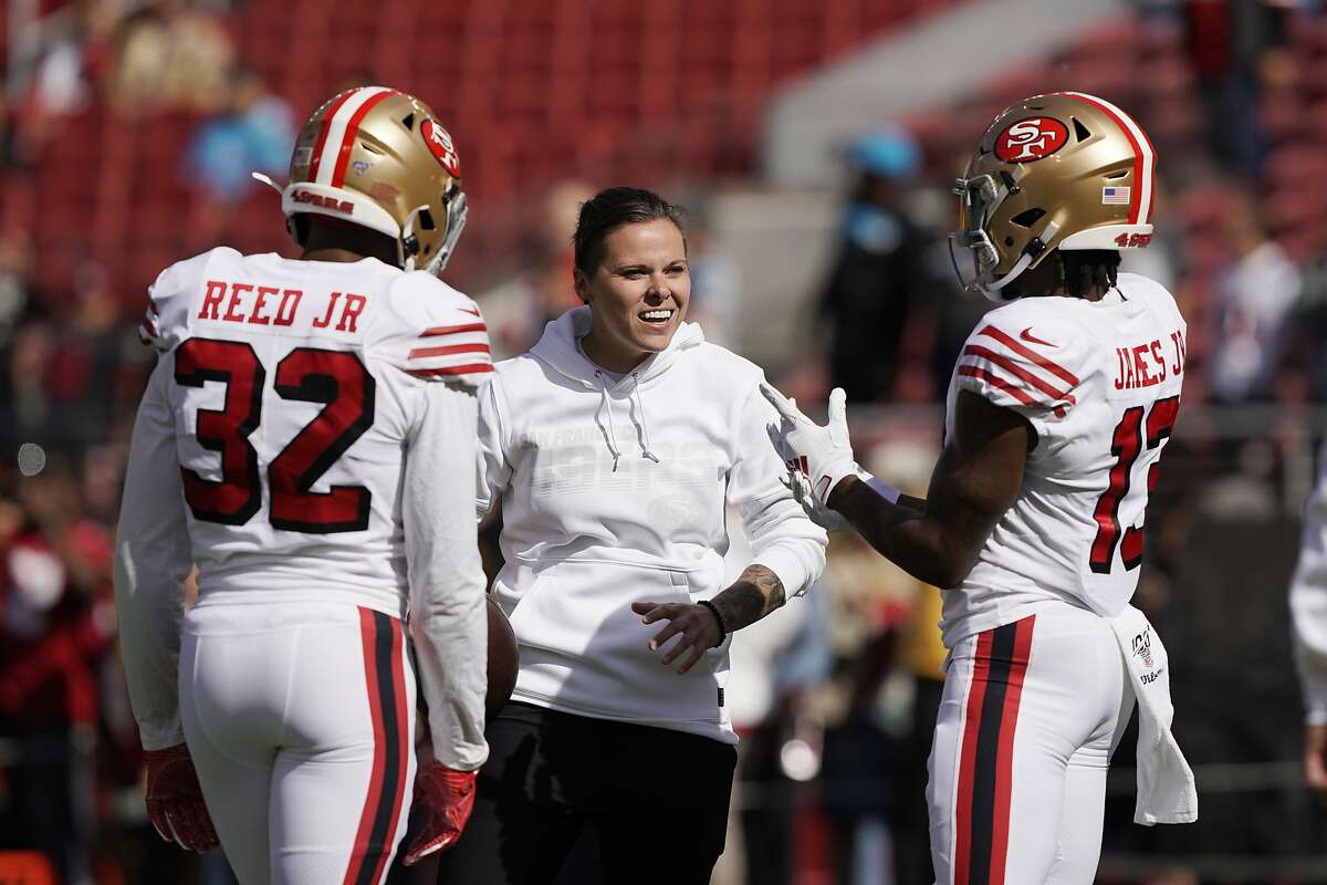 San Francisco 49ers assistant Katie Sowers talks with free safety D.J. Reed (32) and wide receiver Richie James (13) before an NFL football game against the Carolina Panthers in Santa Clara, Calif., in this Sunday, Oct. 27, 2019, file photo.